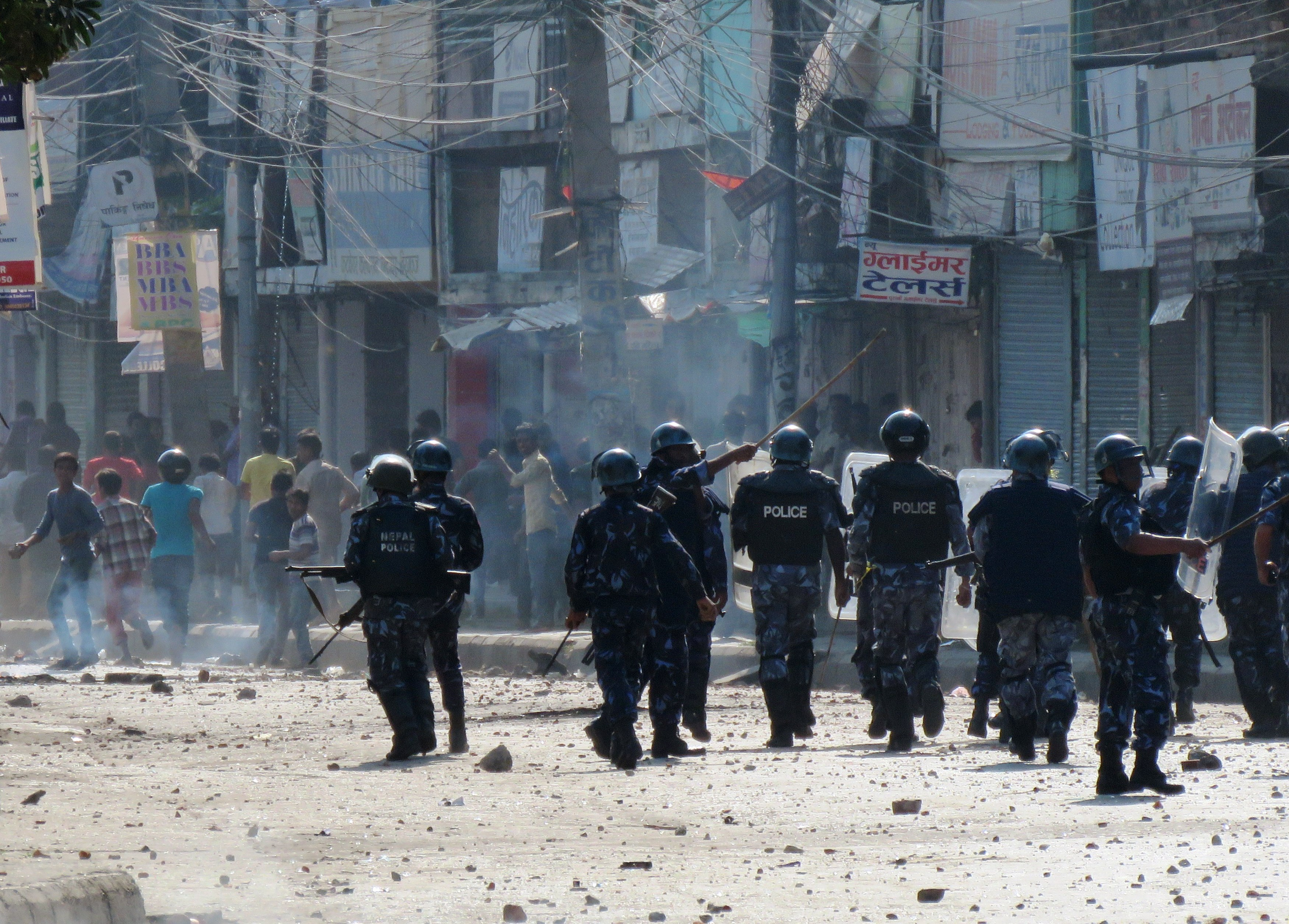 Nepalese police walk by protesters throwing rocks during clashes near the Nepal-India border at Birgunj, on Nov. 2, 2015. Police fired into a crowd of protesters trying to block a key border checkpoint and killed an Indian civilian as anger over a new constitution boiled over.