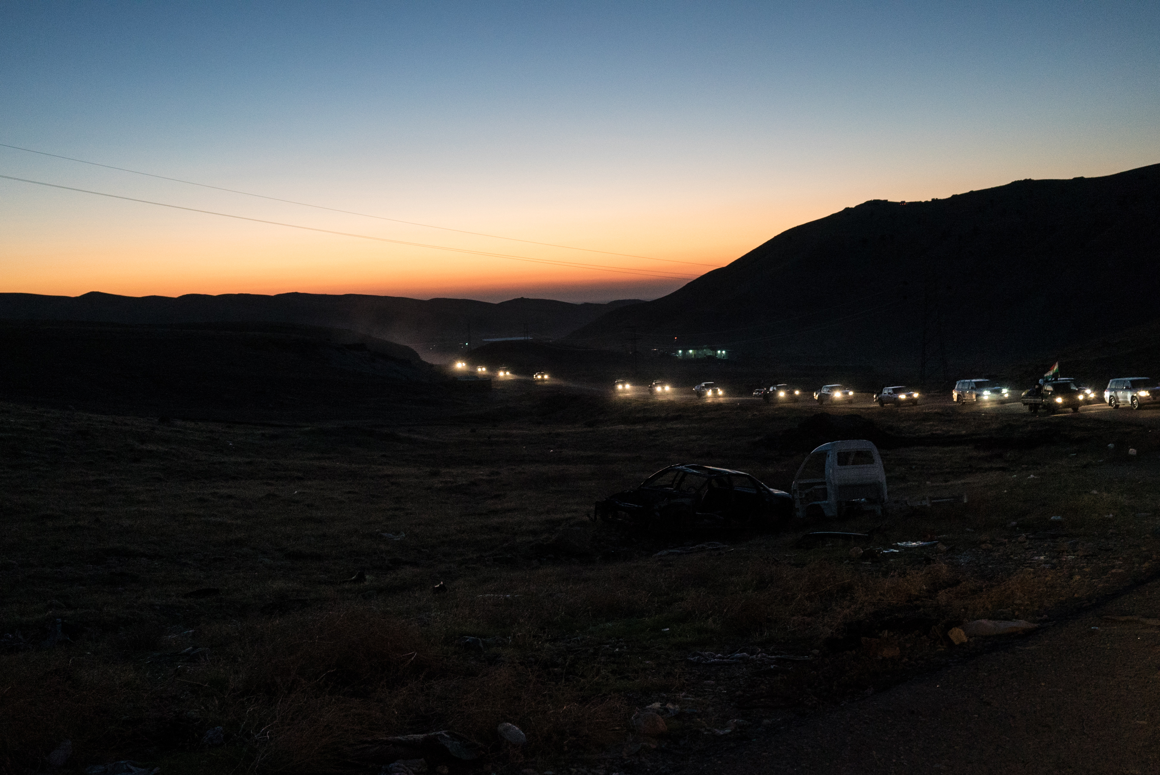 A convoy of Kurdish forces drives to a gathering point before dawn, ahead of a major offensive launched to expel ISIS militants from Sinjar, on Nov 12, 2015.