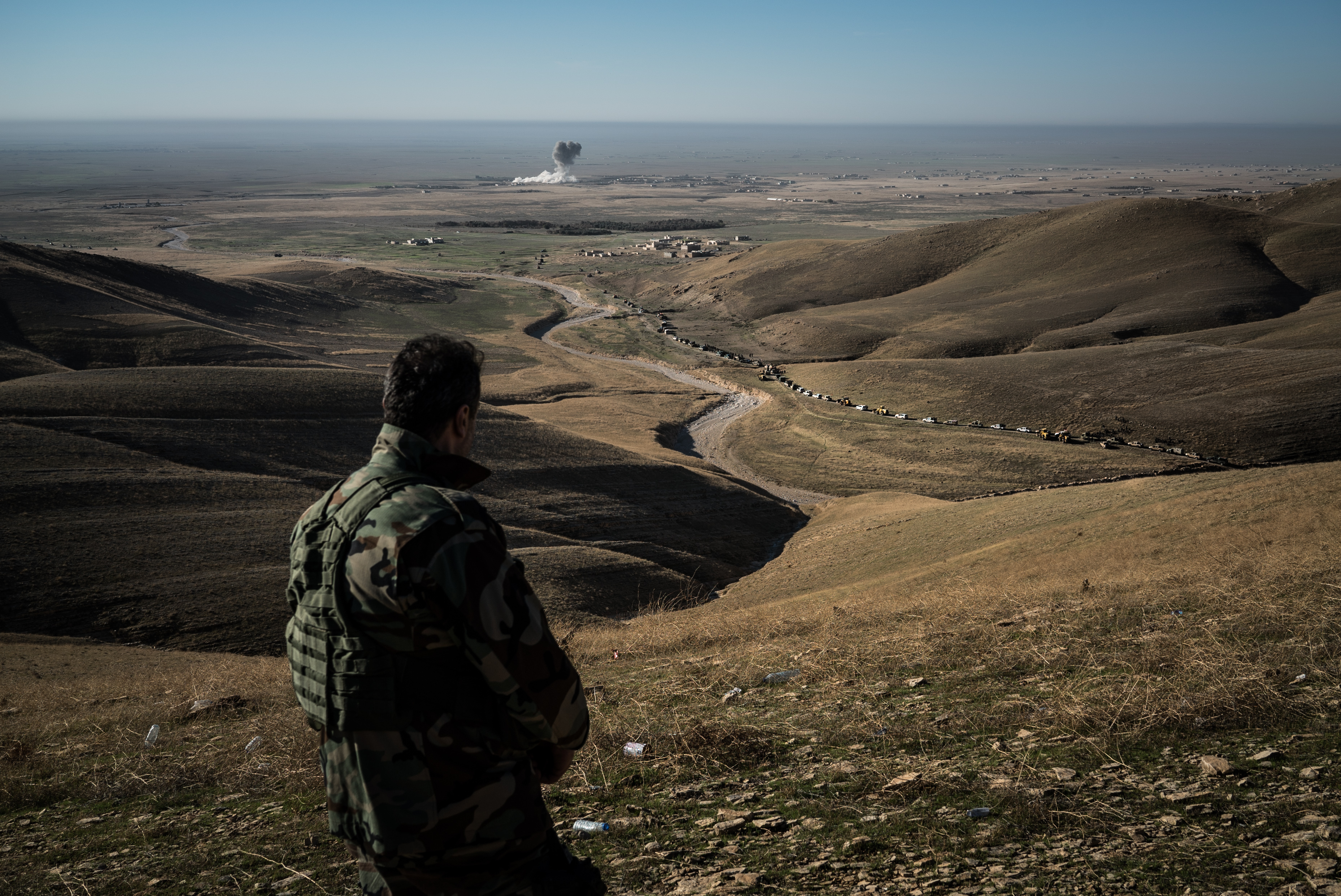 A member of a Kurdish special forces regiment watches from a hilltop as US-led coalition airstrike targets an ISIS position in Sinjar on Nov. 12, 2015.