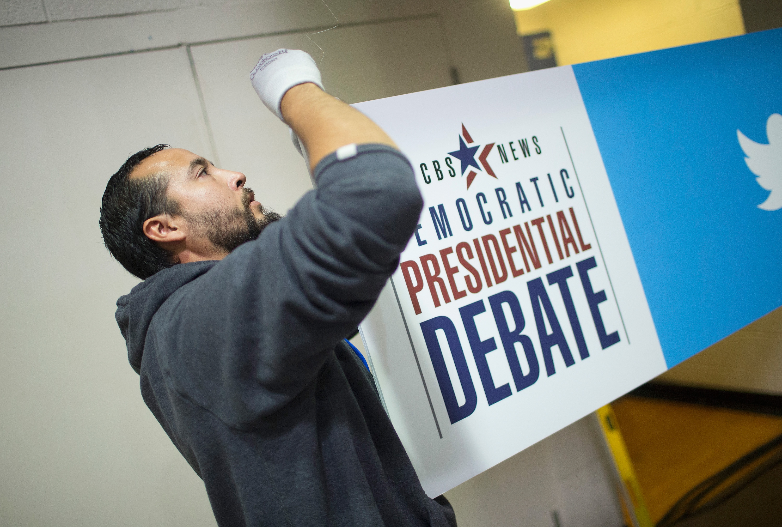 Daniel Rodriguez hangs a sign in the media file center being constructed on the campus of Drake University for tomorrows Democratic presidential debate on November 13, 2015 in Des Moines, Iowa. The debate will be the second for the democratic candidates seeking the nomination for president.