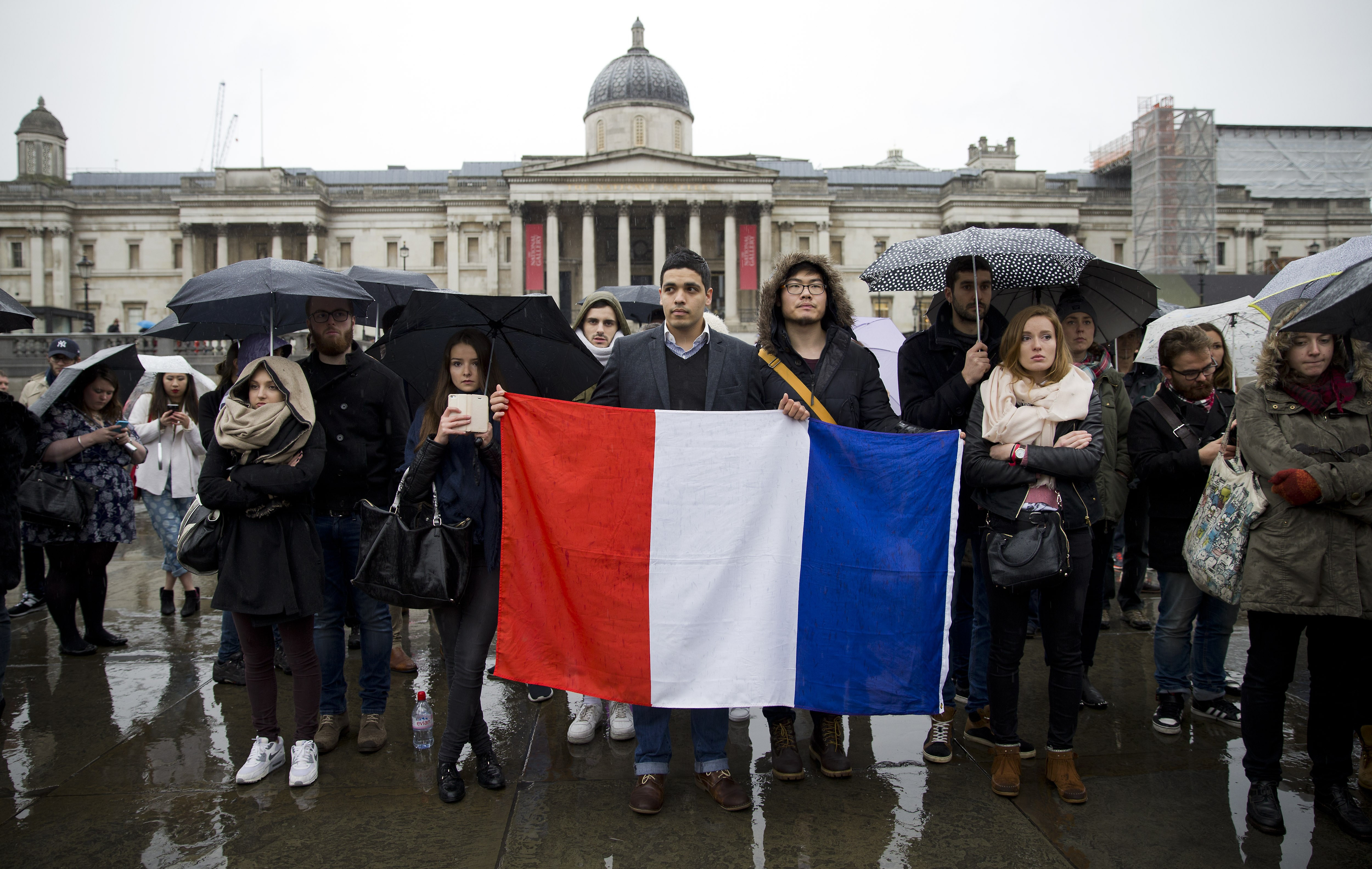 People hold a French national flags as they gather in Trafalgar Square, central London on Nov. 14, 2015.