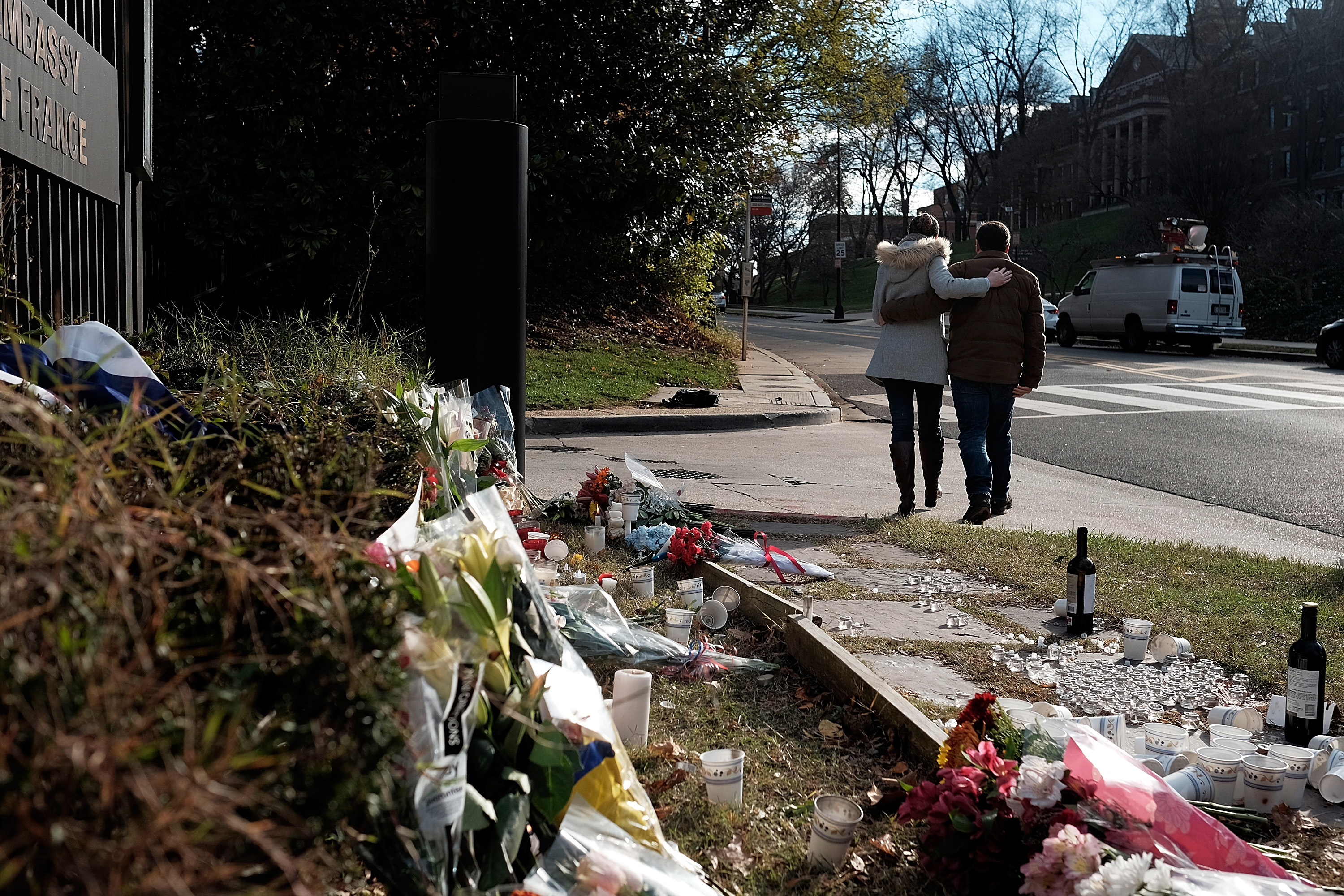 Two people embrace after paying respects at the French Embassy in Washington, DC on Nov. 14, 2015.