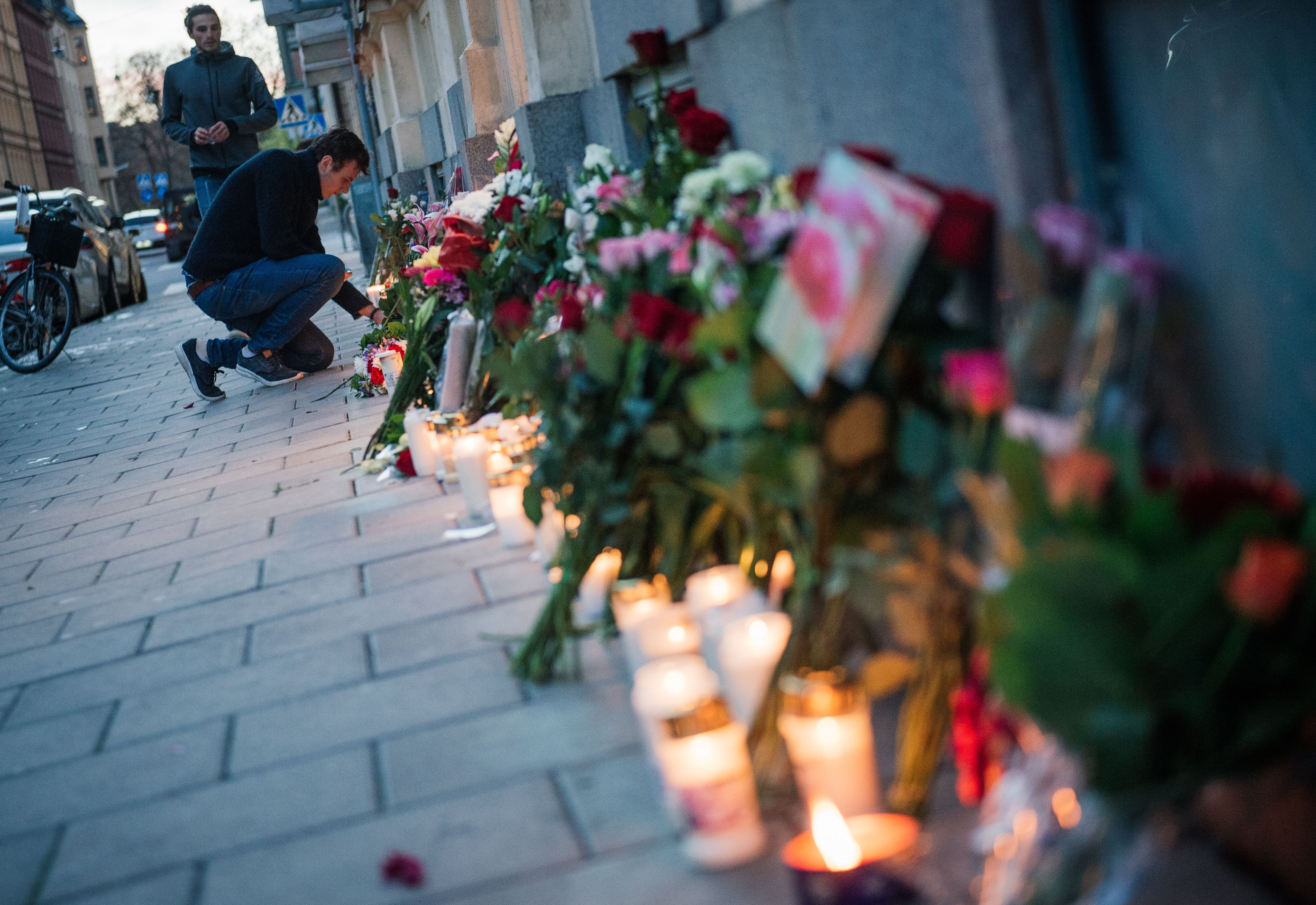 A man places candles and flowers outside the French embassy in Stockholm, Sweden on Nov. 14, 2015.
