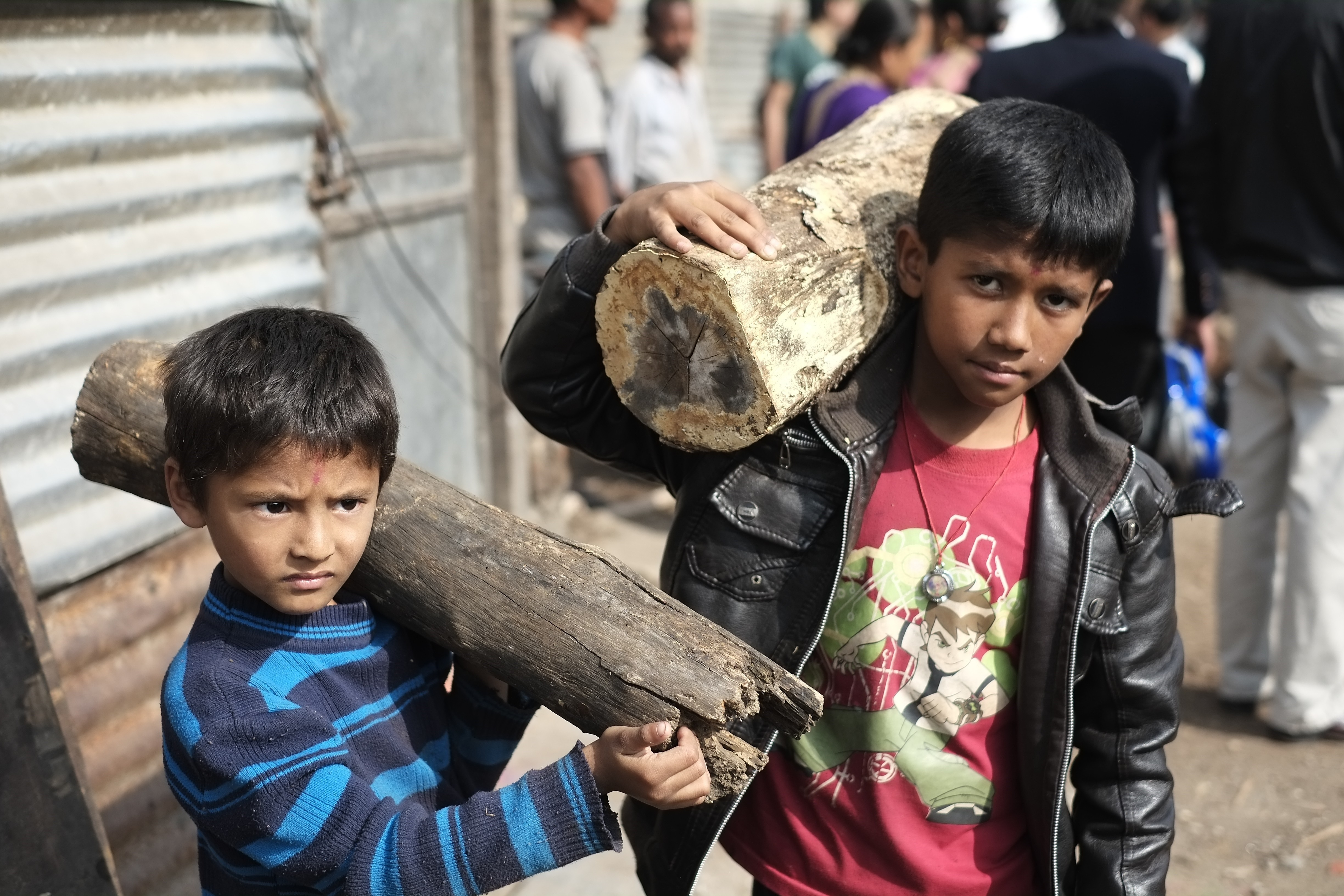 Nepalese boys carry firewood sold by the Nepal government in Kathmandu, Nepal on November 15, 2015. Nepal is facing fuel shortage due to a blockade by India as protests continue in the southern Terai region over the past three months.
