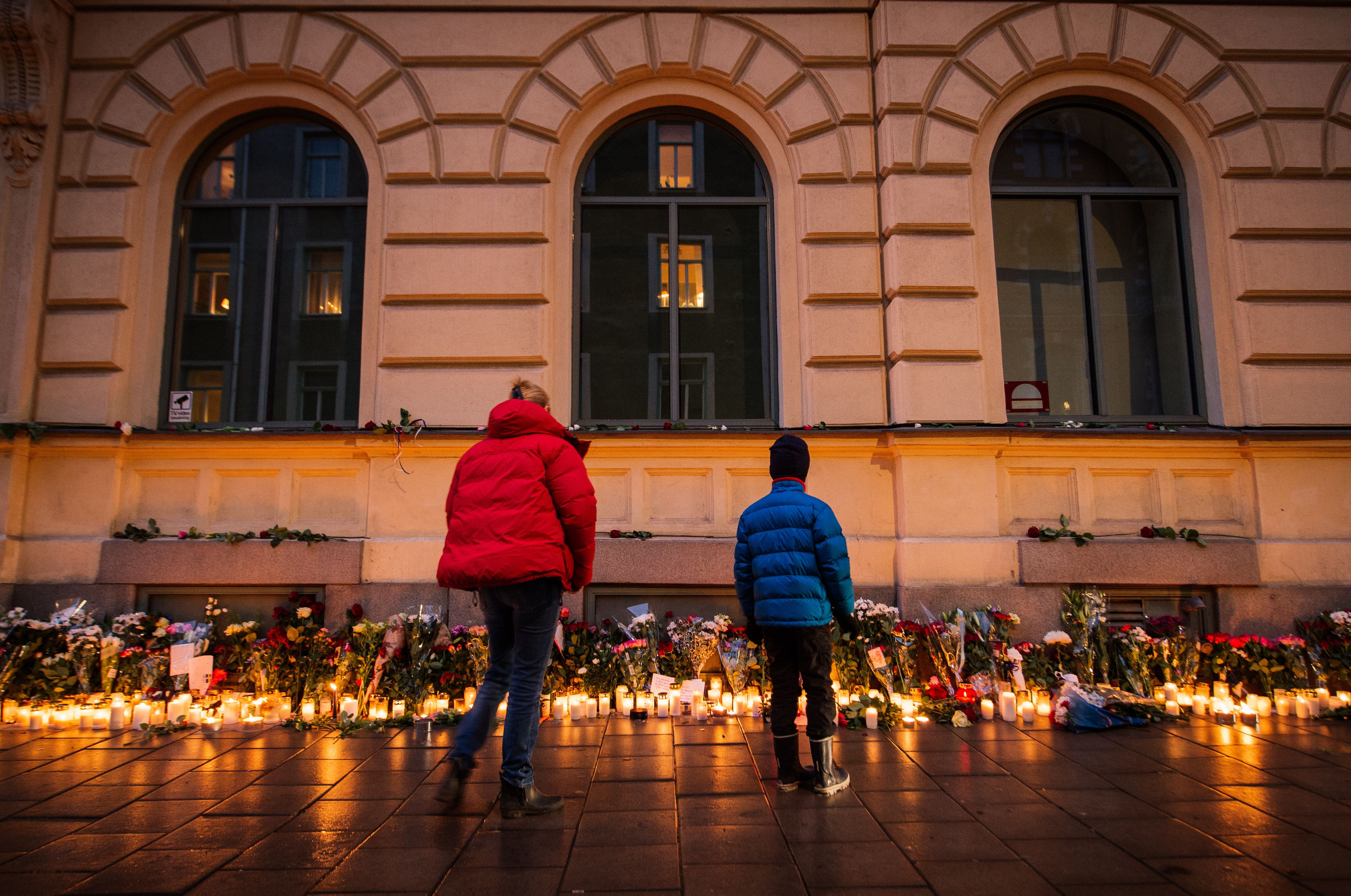 People look at candles and flowers placed outside the French embassy in Stockholm, on November 15, 2015, two days after the deadly attacks in Paris.