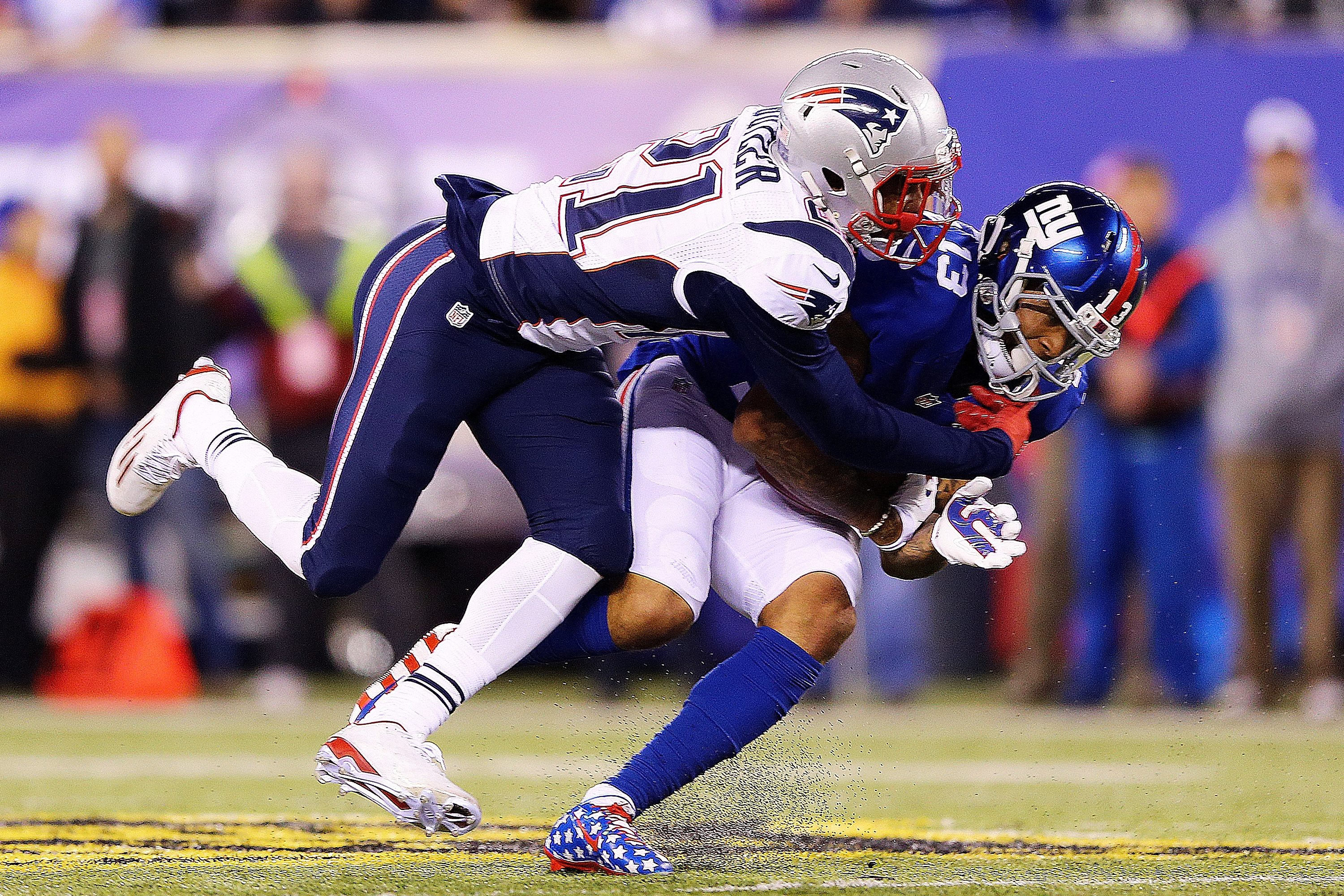 Odell Beckham #13 of the New York Giants is tackled by Malcolm Butler #21 of the New England Patriots during the third quarter at MetLife Stadium on November 15, 2015 in East Rutherford, New Jersey.