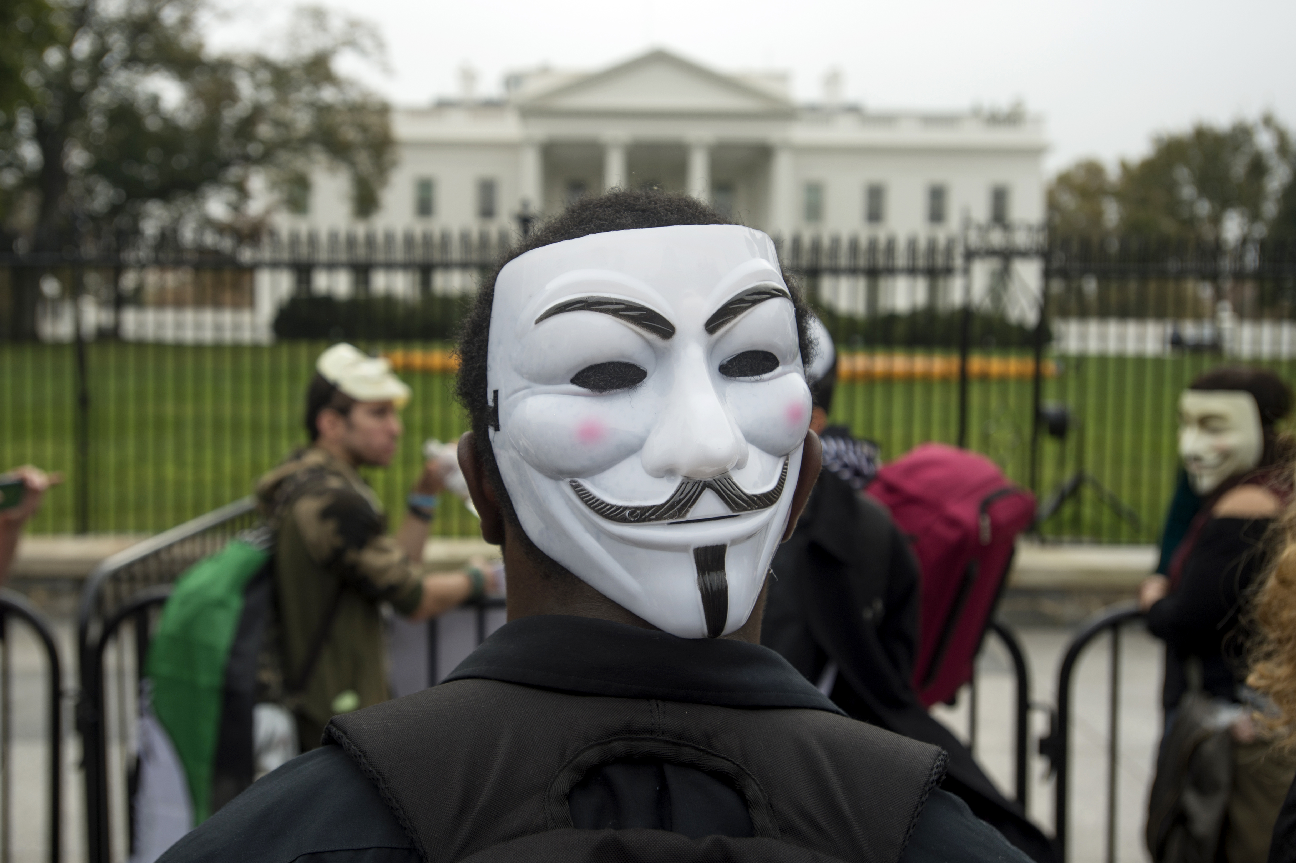 A youth wears a mask on the back of his head while attending a rally outside the White House in Washington, DC, Nov. 5 2015.