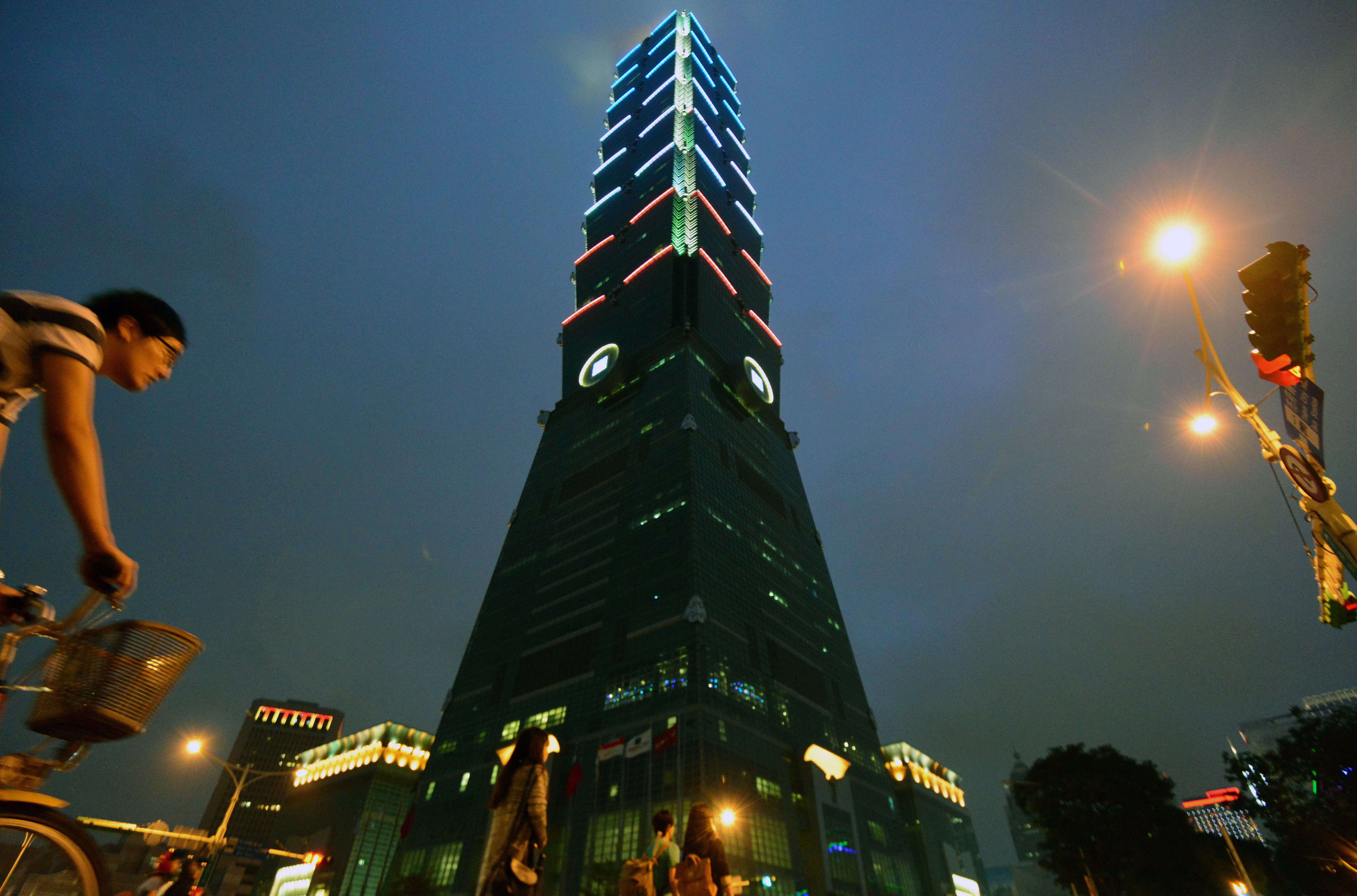 A man rides next to the Taipei 101 building in Taipei, Taiwan, as it lit up with the colors of the French flag on Nov. 14, 2015.