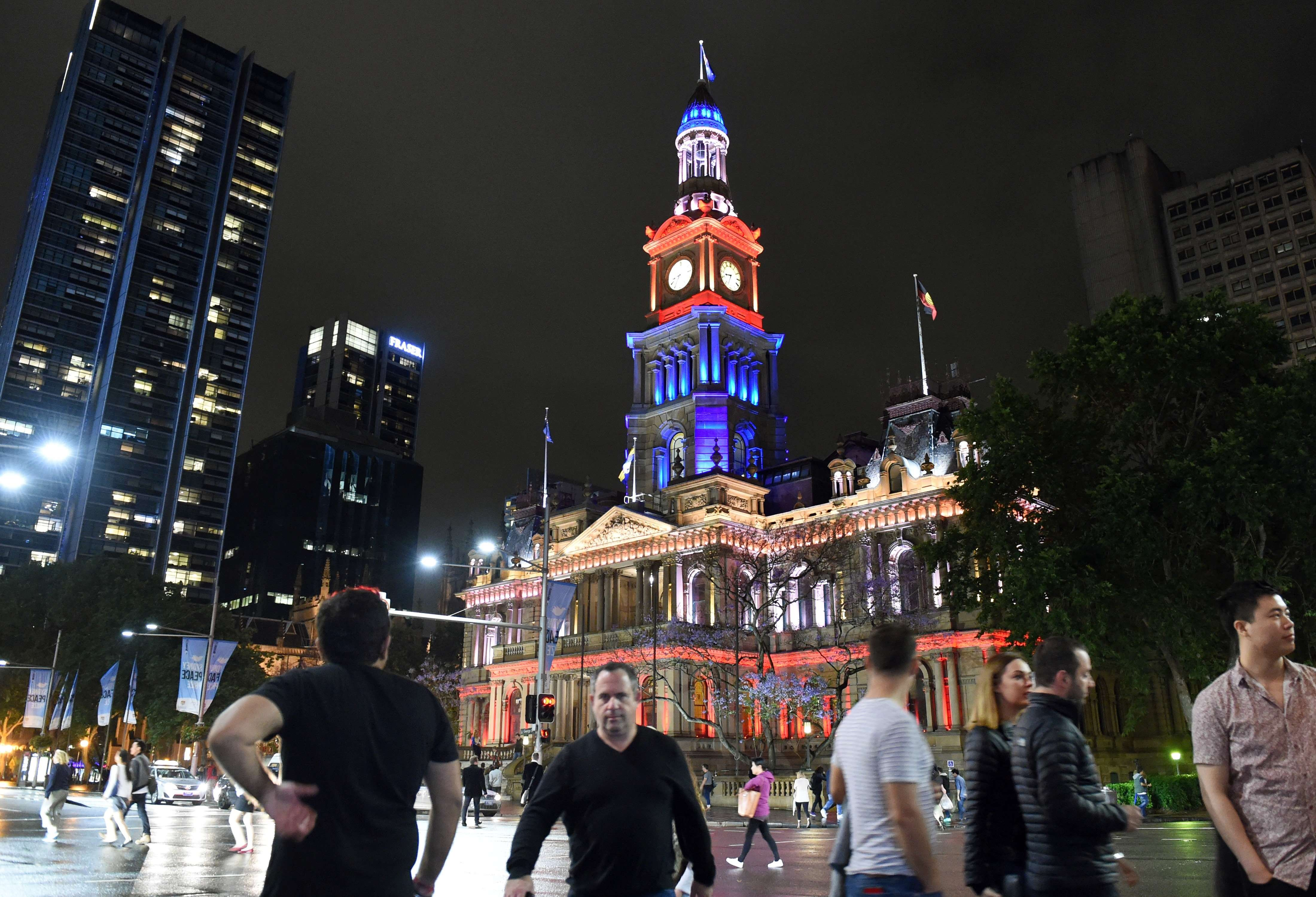 People walk past the Sydney Town Hall as it is lit in red, white and blue, resembling the colors of the French flag in Sydney, Australia on Nov. 14, 2015.