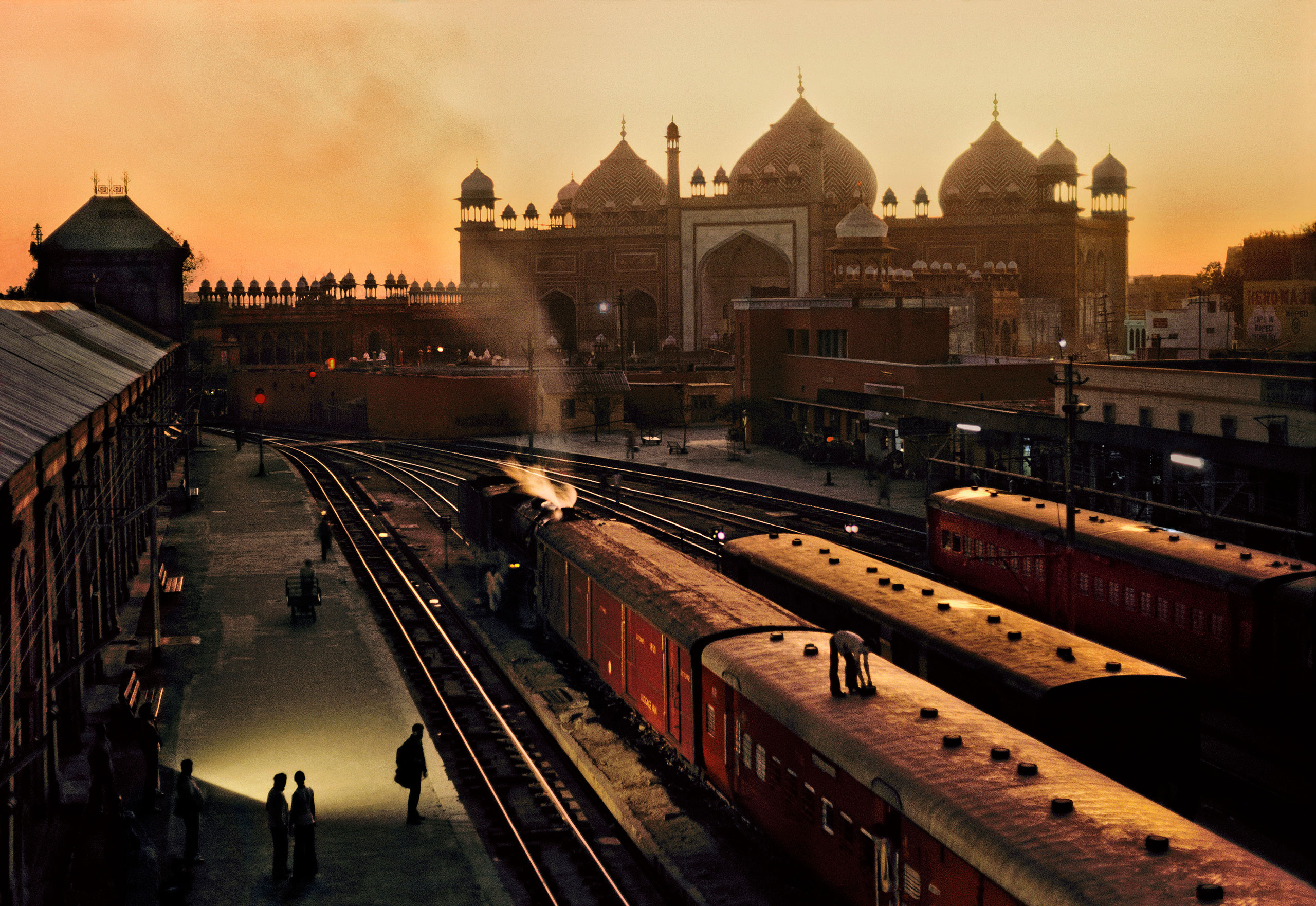 Agra Fort train station at dusk, with the Jama Masjid, the great mosque of Shah Jahan, in the distance.                               Agra, Uttar Pradesh, 1983