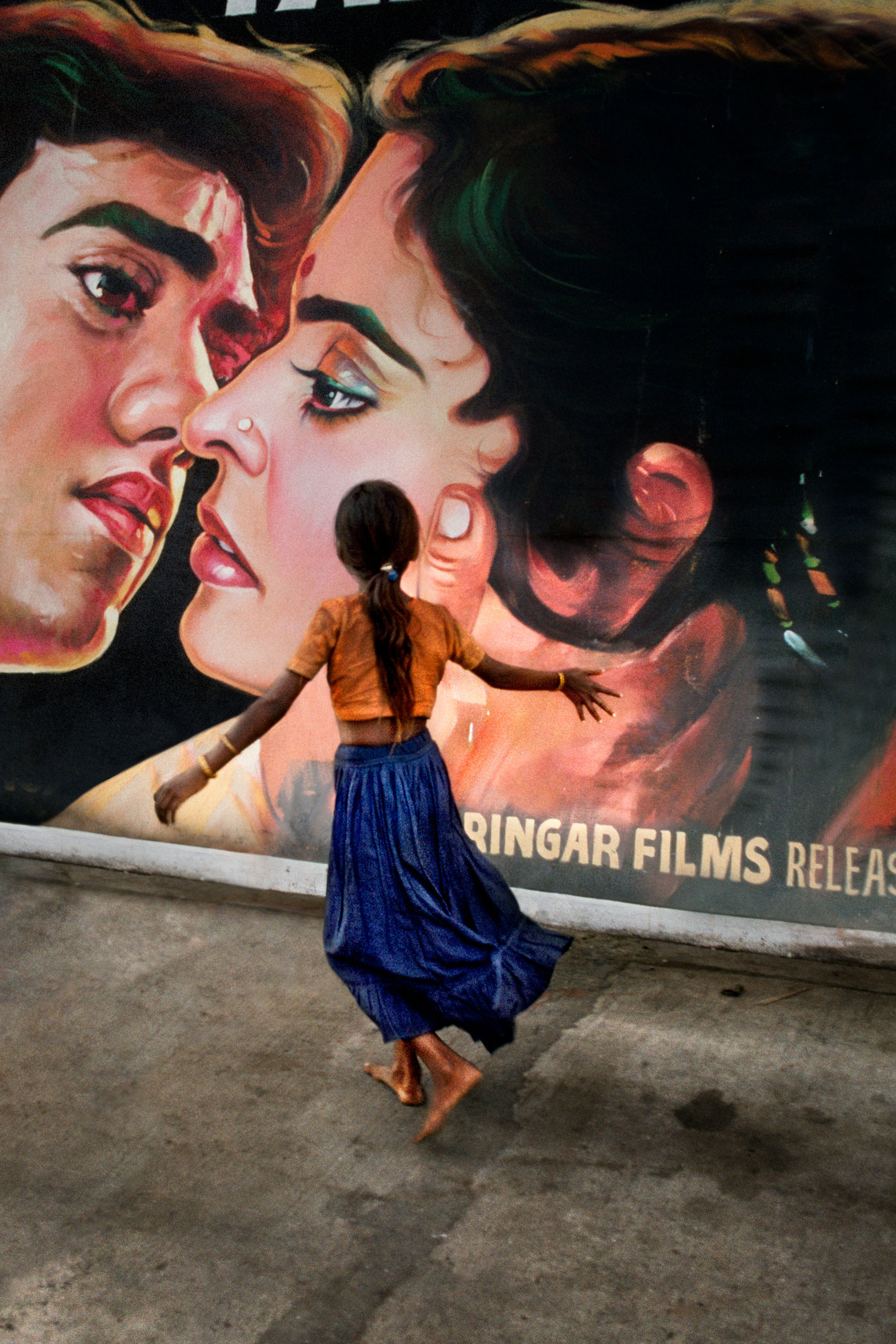 A young girl walking past a movie poster Mumbai, 1993