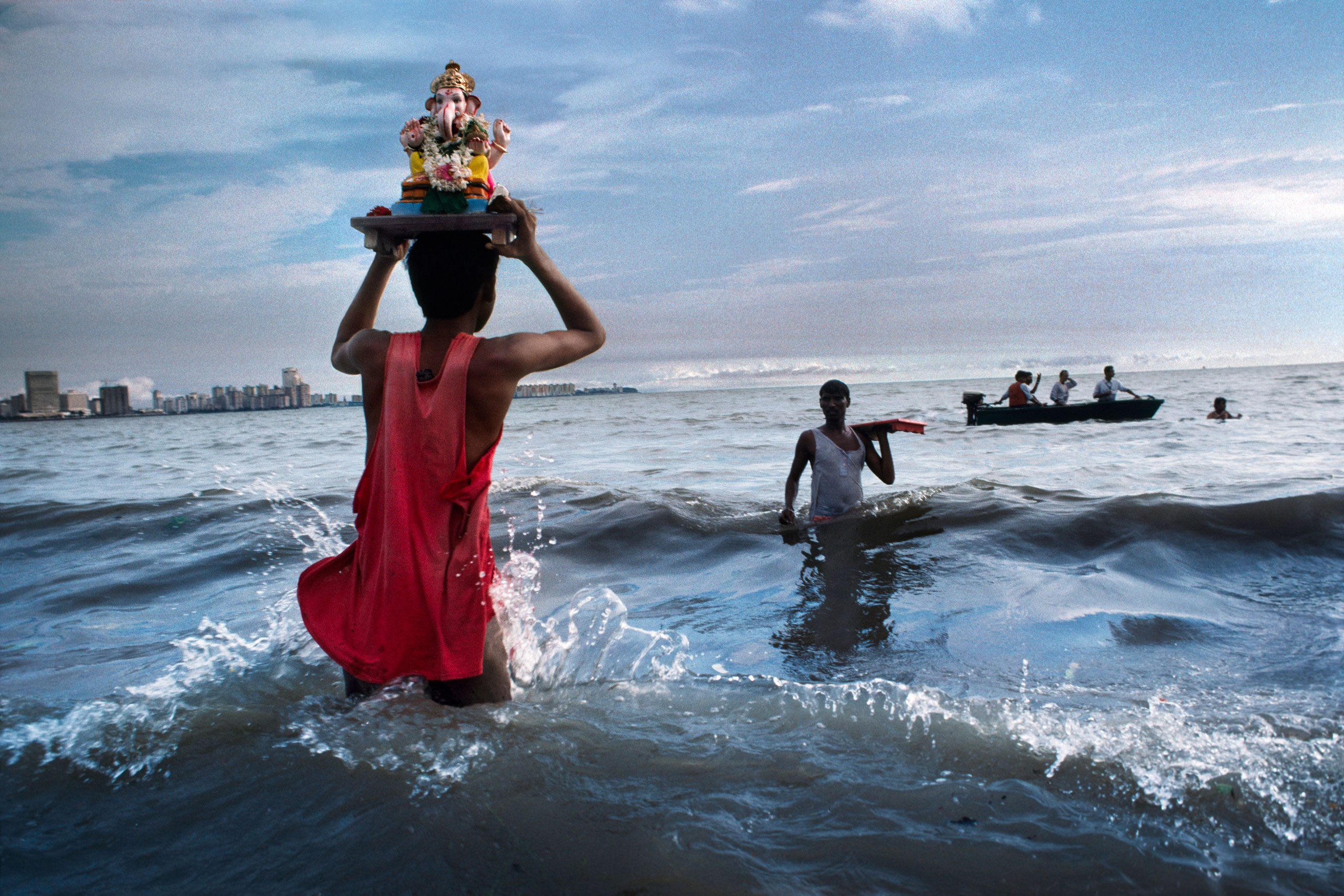 Devotee carries statue of Lord Ganesh into the waters of the Arabian Sea during the immersion ritual off Chowpatty beach.                               Mumbai, 1993