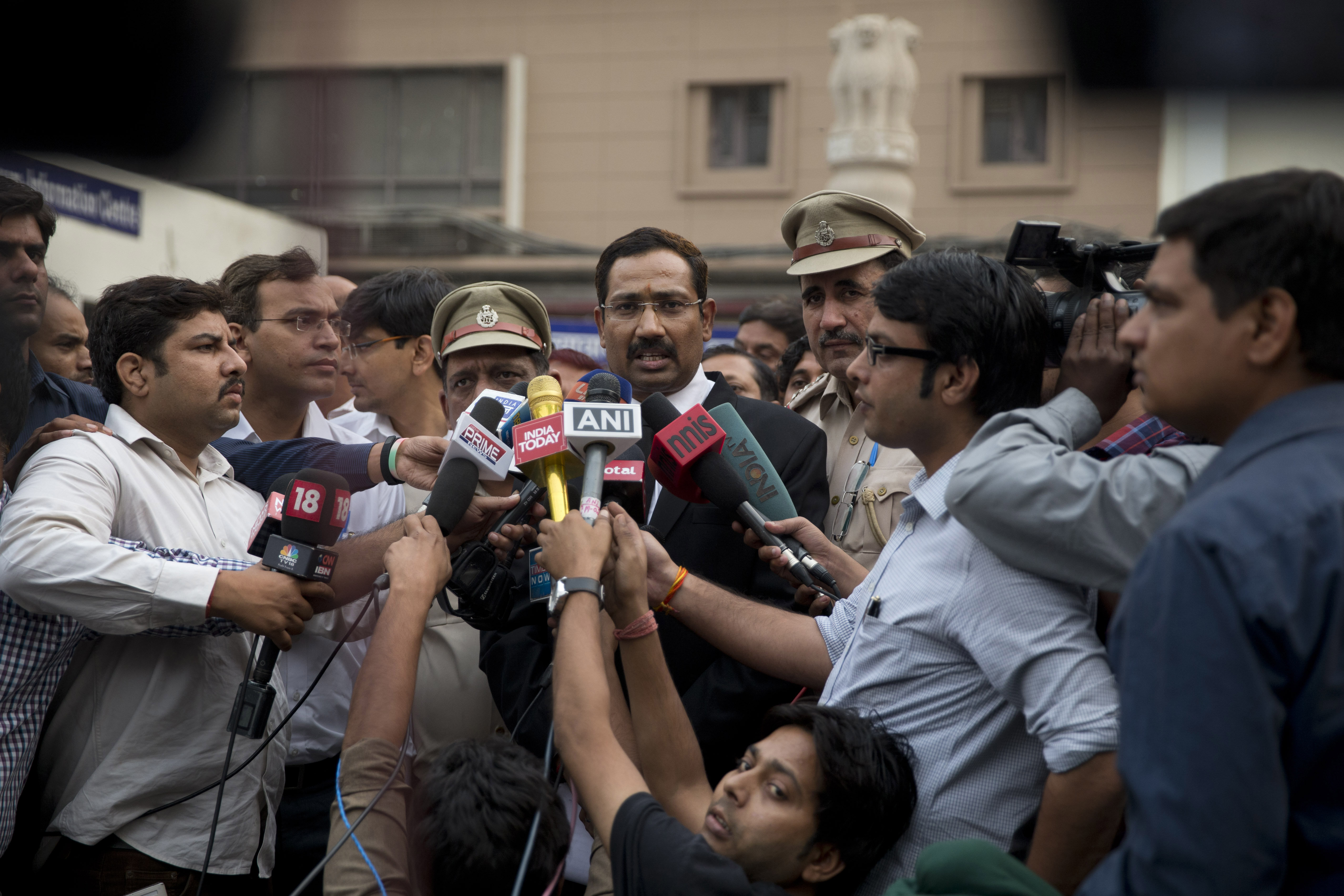 A lawyer, center, speaks to reporters at the Tis Hazari Courts premises, after a court sentence for Uber driver Shiv Kumar Yadav in New Delhi on Tuesday, Nov. 3, 2015. An Indian court sentenced Uber driver Yadav to life in prison Tuesday for raping a passenger in his vehicle last December.