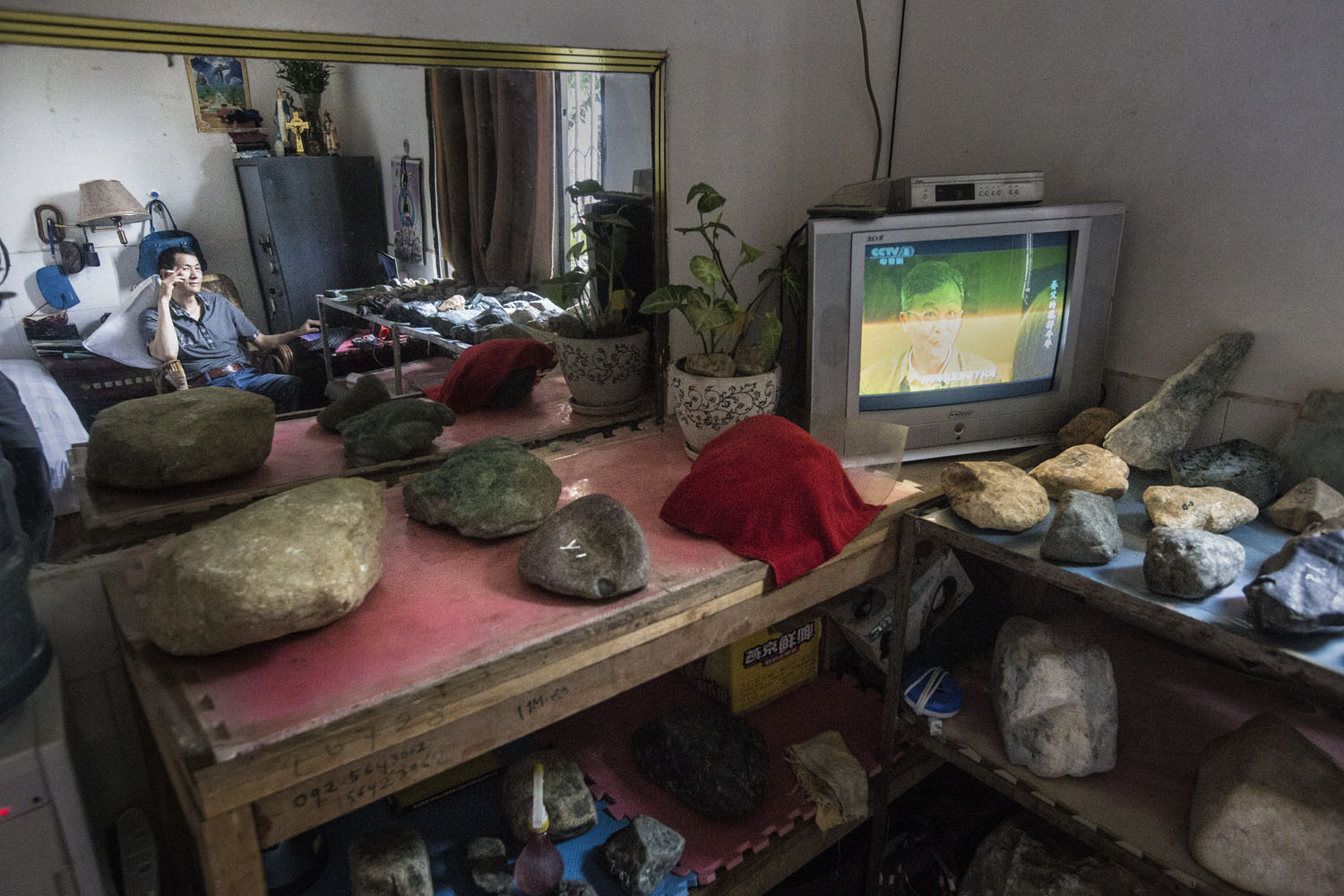 A Chinese trader waits for customers in hotel room where he rents to keep the raw jade stones which are smuggled from Kachin State, at a hotel in Yin Jiang, China, June 2015.