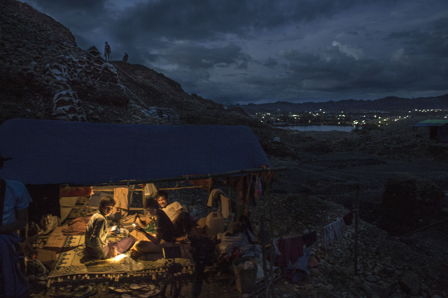 Jade miners rest inside their tents where they sleep to guard their mining plots from strangers as night falls, Hpakant, July 2014