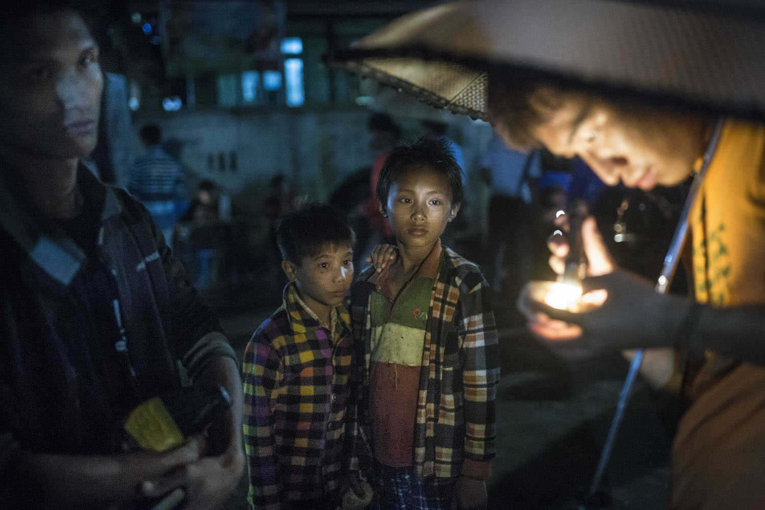 Seven-year-old Breng Aung and his brother who lives in a Kachin refugee camp in a Kachin baptist church in Lone Khin, wait as a jade buyer inspect the stone that they are trying to sell at the jade market, in Lone Khin, Hpakant, April 2015. They were trying to sell the small low quality stones for 2,000 kyats ($2)