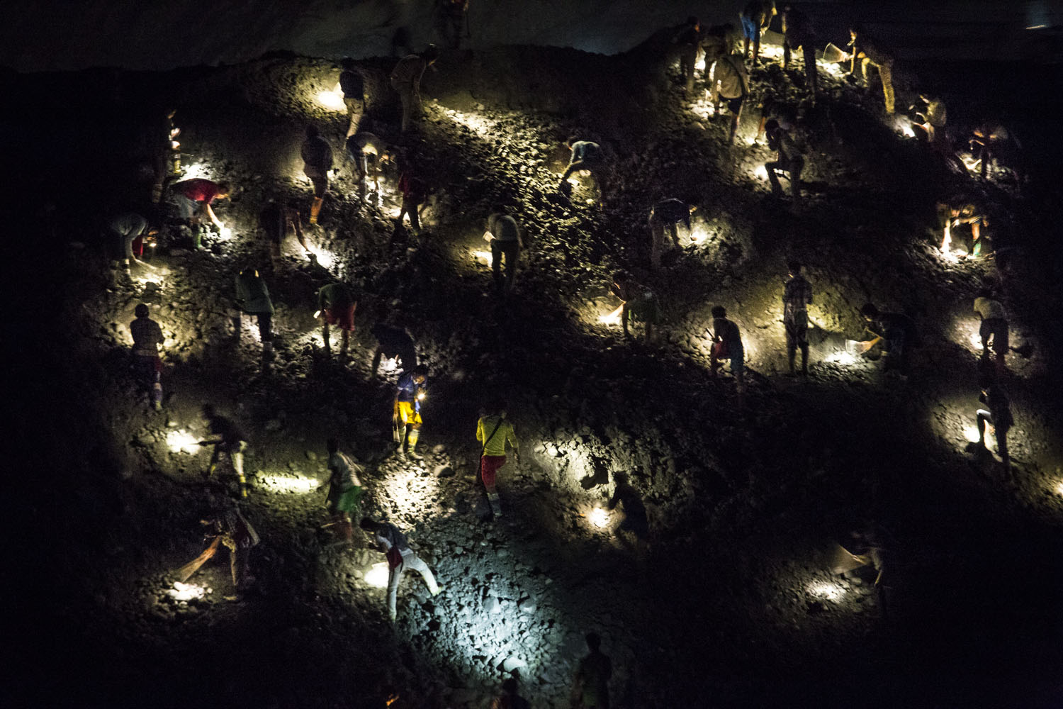 Miners with torchlights on their heads go over a pile of company mining waste, looking for jade. Hpakant, 2015