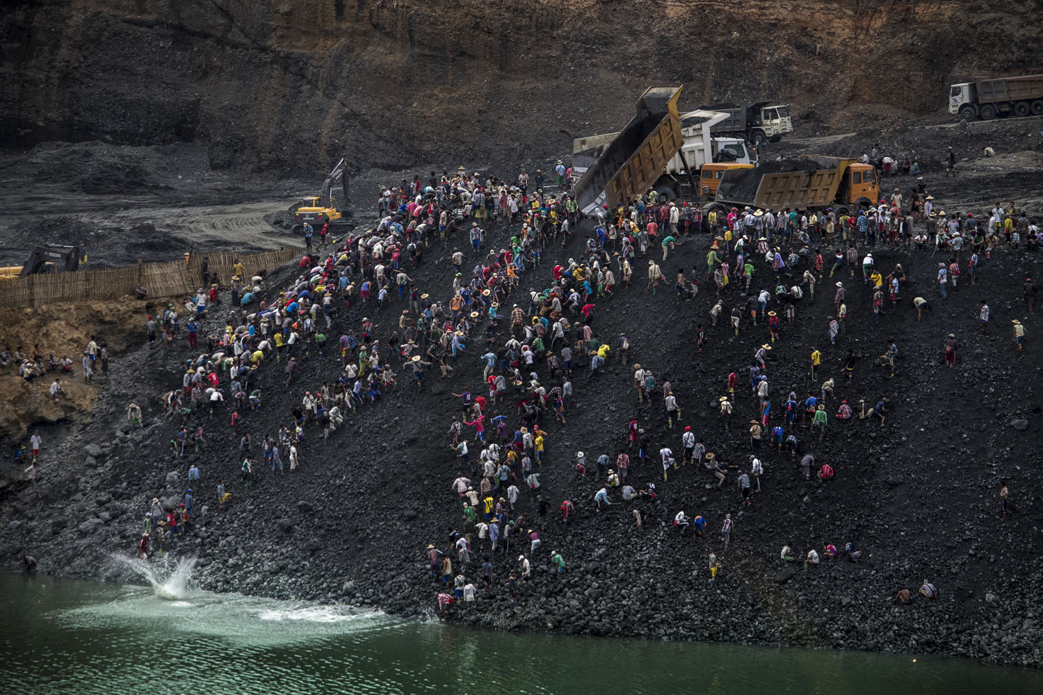 Small-scale miners search for stone as dump trucks from Myanmar Sein Lei Aung mining company dump waste in Hmaw Si Zar, Lone Khin, Hpakant, April 2015