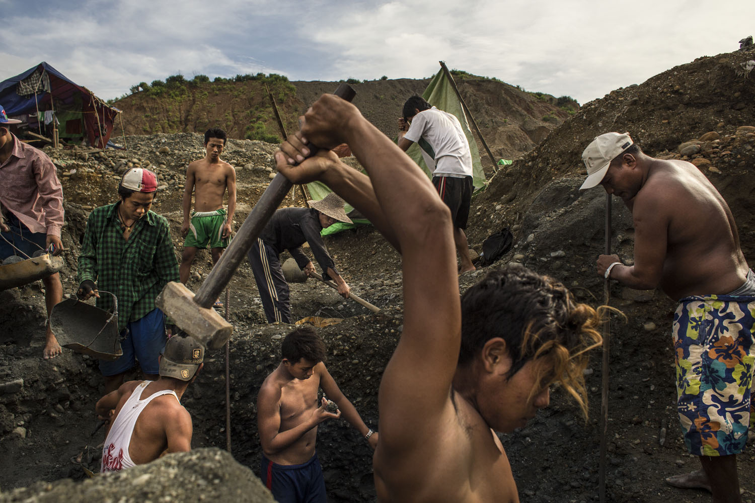 A team of miners work in a jade mine. Some miners work alone while some like this young men here work by a team in a small plot land that is owned by their 'Lao-ban' (meaning 'Boss' in Chinese), Hpakant, July 2014