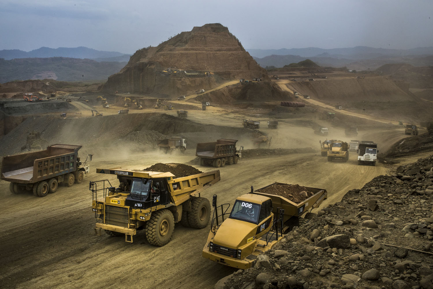 Dump trucks pass by near the Kyaing International company mining site, Sai Ja Bon, Hpakant, April 2015. Kyaing International company is widely known to be owned by the family of former military dictator Than Shwe