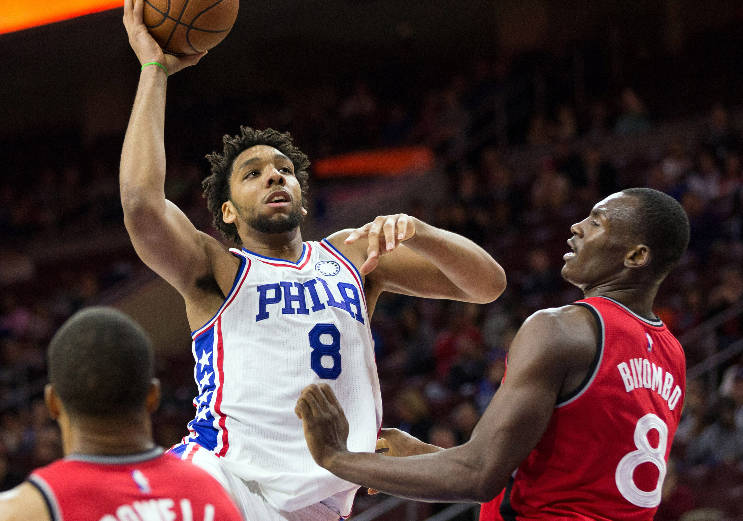 Philadelphia 76ers center Jahlil Okafor shoots against the defense of Toronto Raptors forward Bismack Biyombo during the second half at Wells Fargo Center in Philadelphia on Nov 11, 2015.