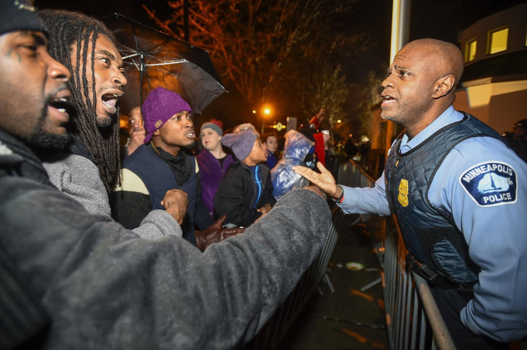 A police officer talks with demonstrators in front of a north Minneapolis police precinct during a protest in response of Sunday's shooting death of Jamar Clark by police officers in Minneapolis on Nov. 18, 2015.