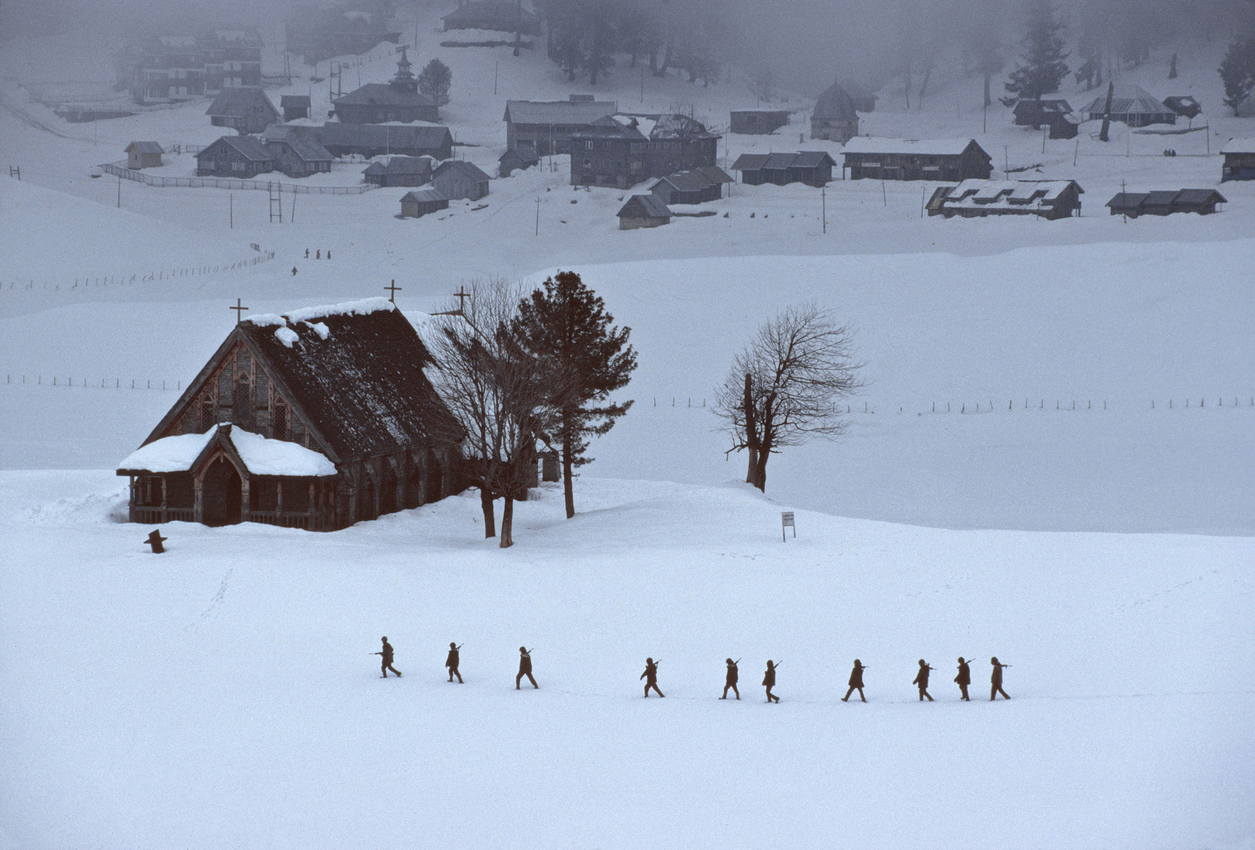 Soldiers trudge through the snow, passing a church, mosque and temple.                               Gulmarg, Kashmir, 1999