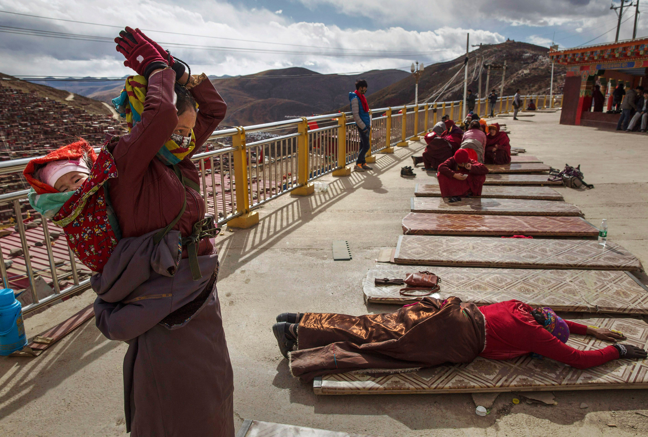 A Tibetan Buddhist nomad woman prostrates at a monastery at the Larung Wuming Buddhist Institute, which is home to thousands of monks and nuns.