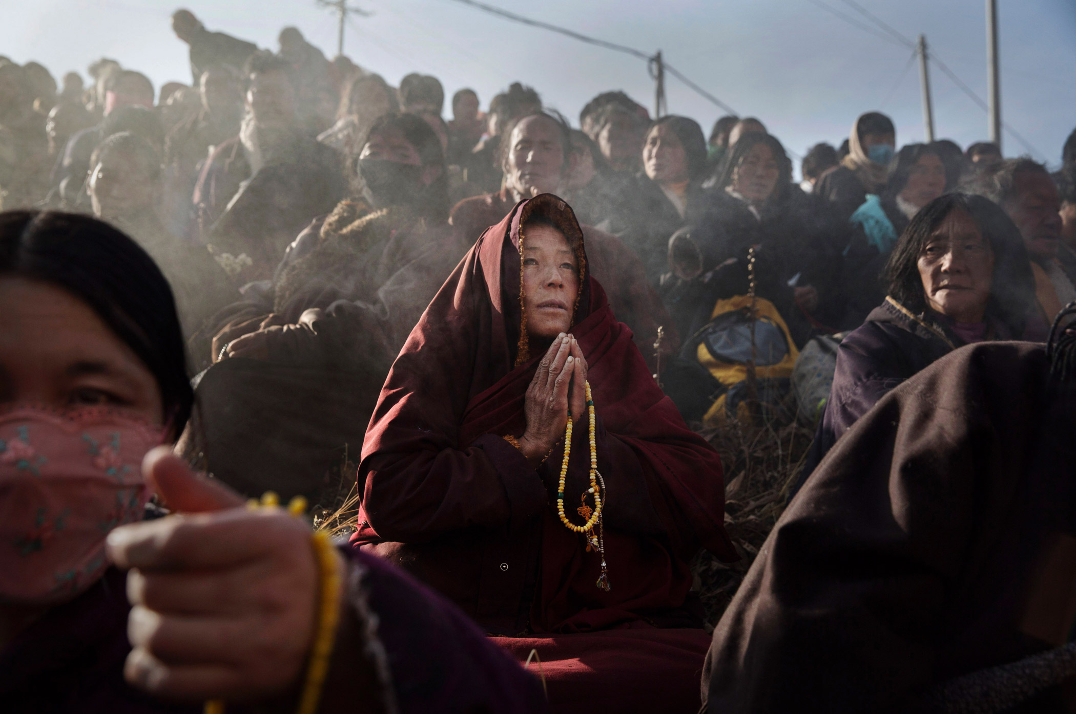 People pray on a hillside during a morning chanting session.