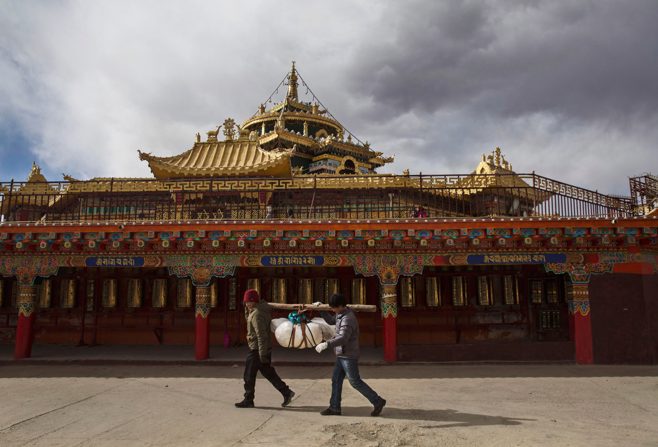 Tibetan Buddhists circumambulate a monastery with the body of a relative before sky burial at the Larung Wuming Buddhist Institute on Oct. 30.