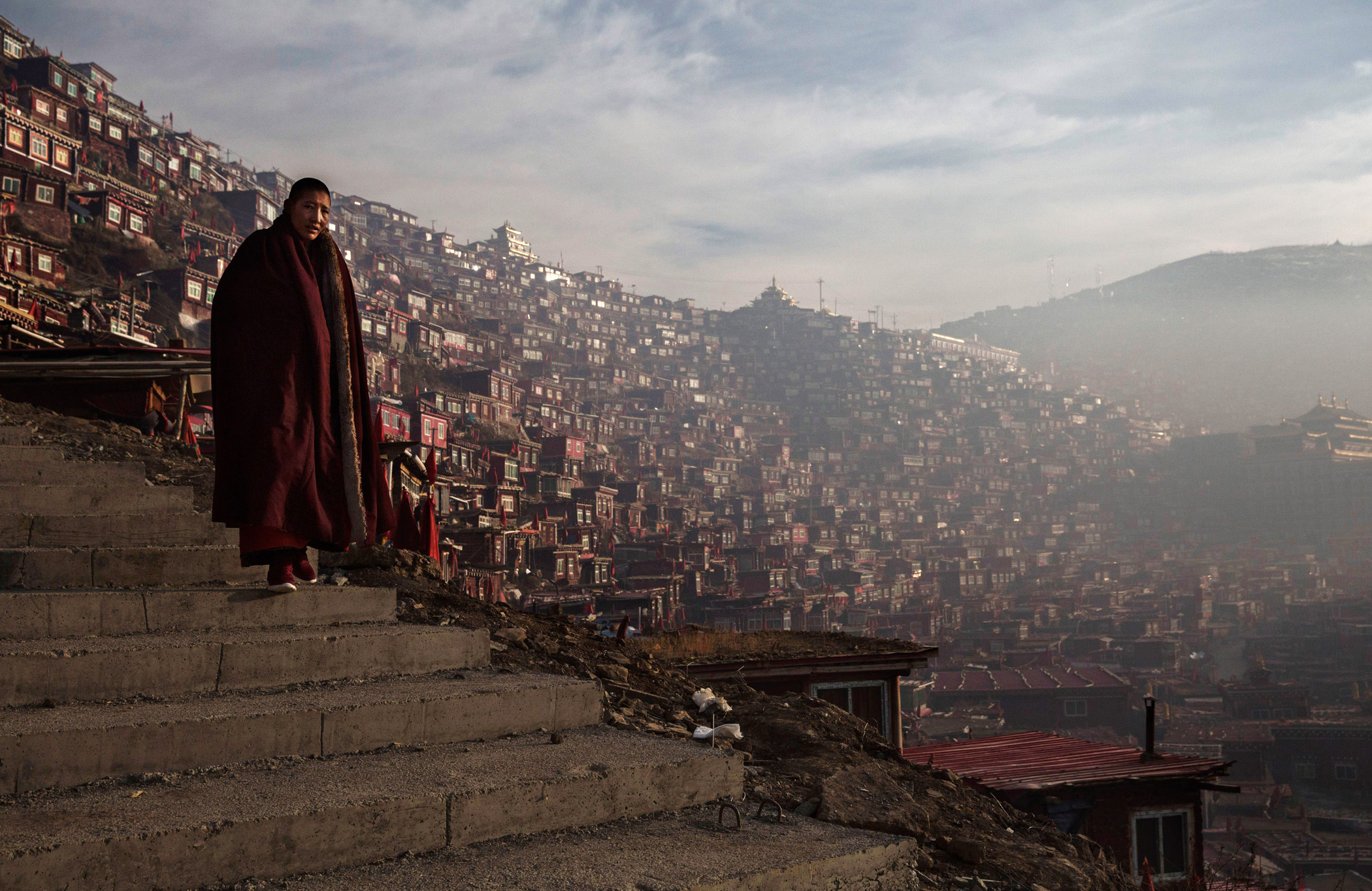 A Tibetan Buddhist nun walks past dwellings on her way to a chanting session.