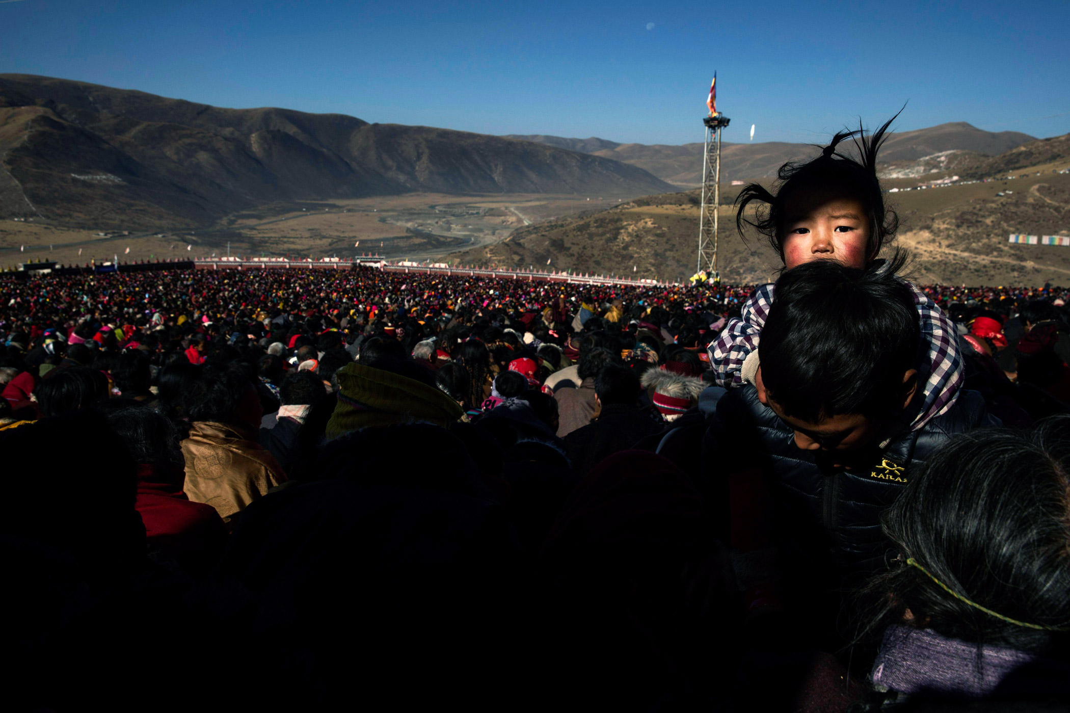 A Tibetan Buddhist nomad carries his daughter in the crowd on a hillside during the annual Bliss Dharma Assembly.