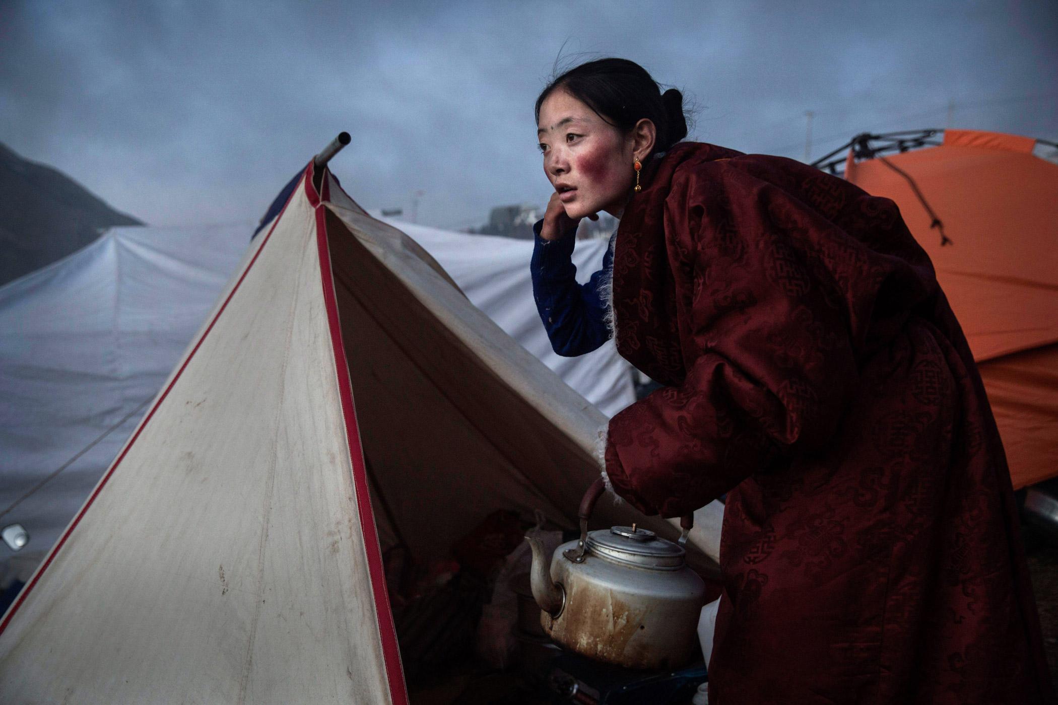 A Tibetan Buddhist nomad woman prepares tea at dusk following a chanting session.