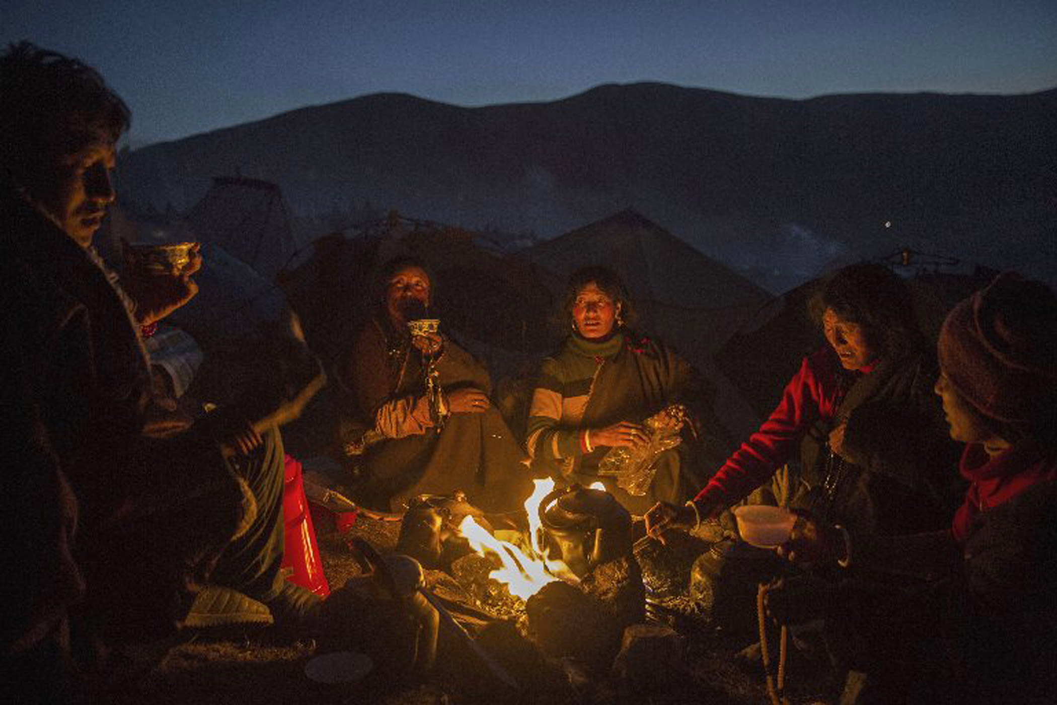 Tibetan Buddhist nomads cook on a fire at dusk during the annual Bliss Dharma Assembly.