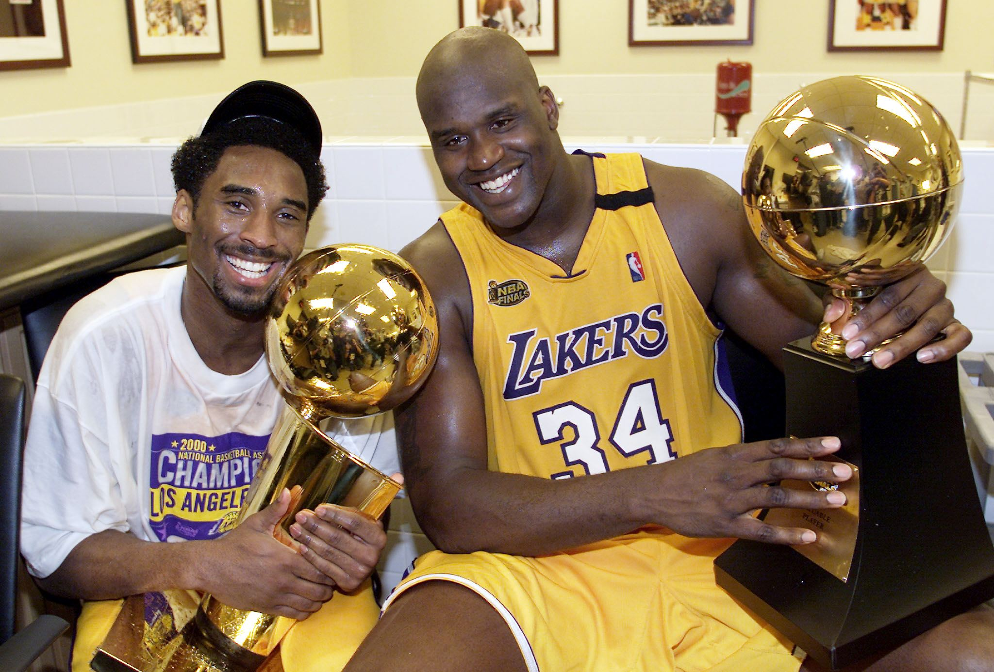 Bryant (left) holds the Larry O'Brian trophy as teammate Shaquille O'Neal holds the MVP trophy after winning their first NBA Championship against the Indiana Pacers at Staples Center in Los Angeles on June 19, 2000. It would be the first of three consecutive titles for the star duo.