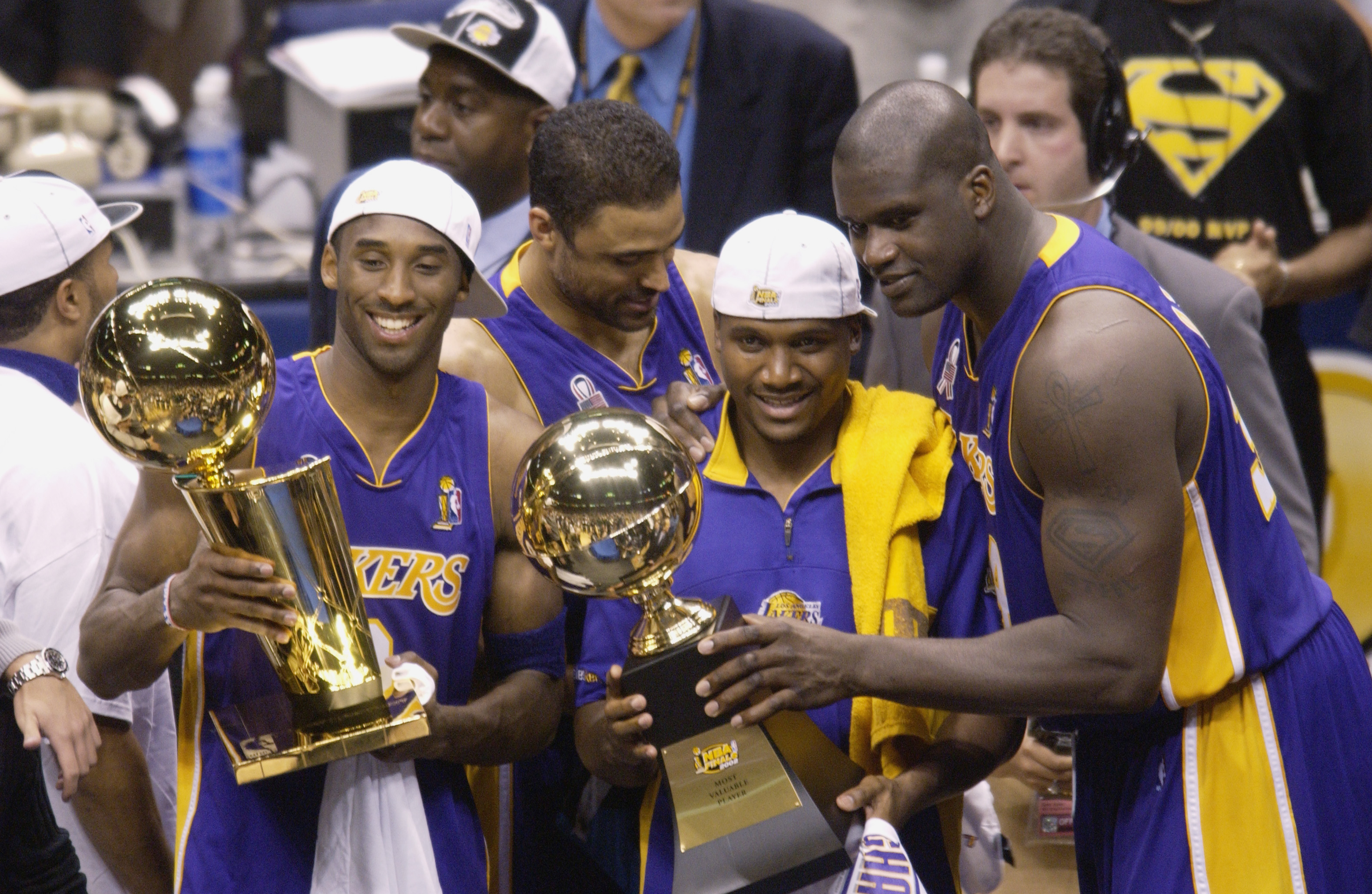 Bryant, Lindsey Hunter and Shaquille O'Neal celebrate their win over the New Jersey Nets in Game four of the 2002 NBA Finals at Continental Airlines Arena in East Rutherford, N.J. on June 12, 2002. Bryant, aside from further cementing his superstar status, became the youngest player to win three NBA titles.