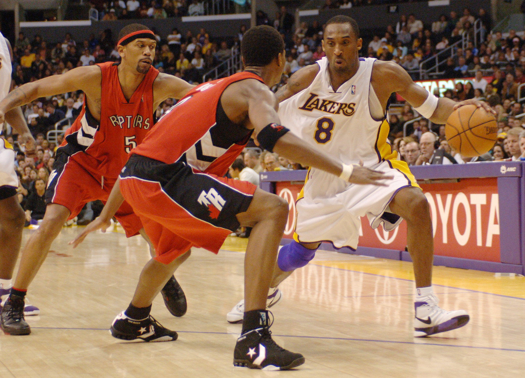 Bryant drives past Toronto Raptors' Jalen Rose and Chris Bosh in the fourth quarter of an NBA basketball game in Los Angeles on Jan. 22, 2006, en route to scoring a career-high 81 points. The performance was not only the best-ever by a Laker, but also the second-highest score in a single game in the NBA.