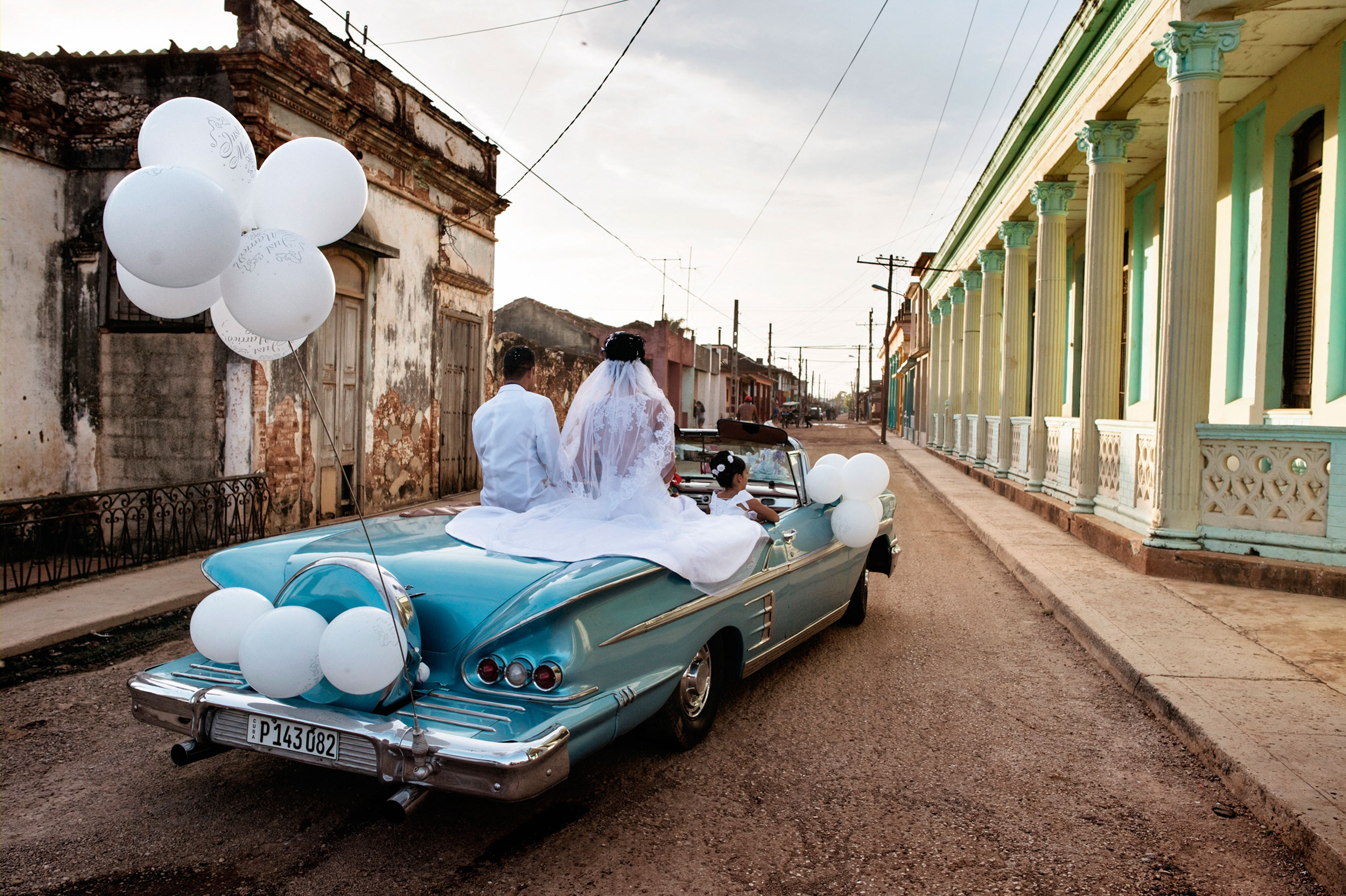 Newlyweds ride in a vintage American car through the streets of Guira de Melena. In this prosperous area outside Havana, weddings can cost as much as $20,000.From  Take a Walk Through the Streets of Cuba