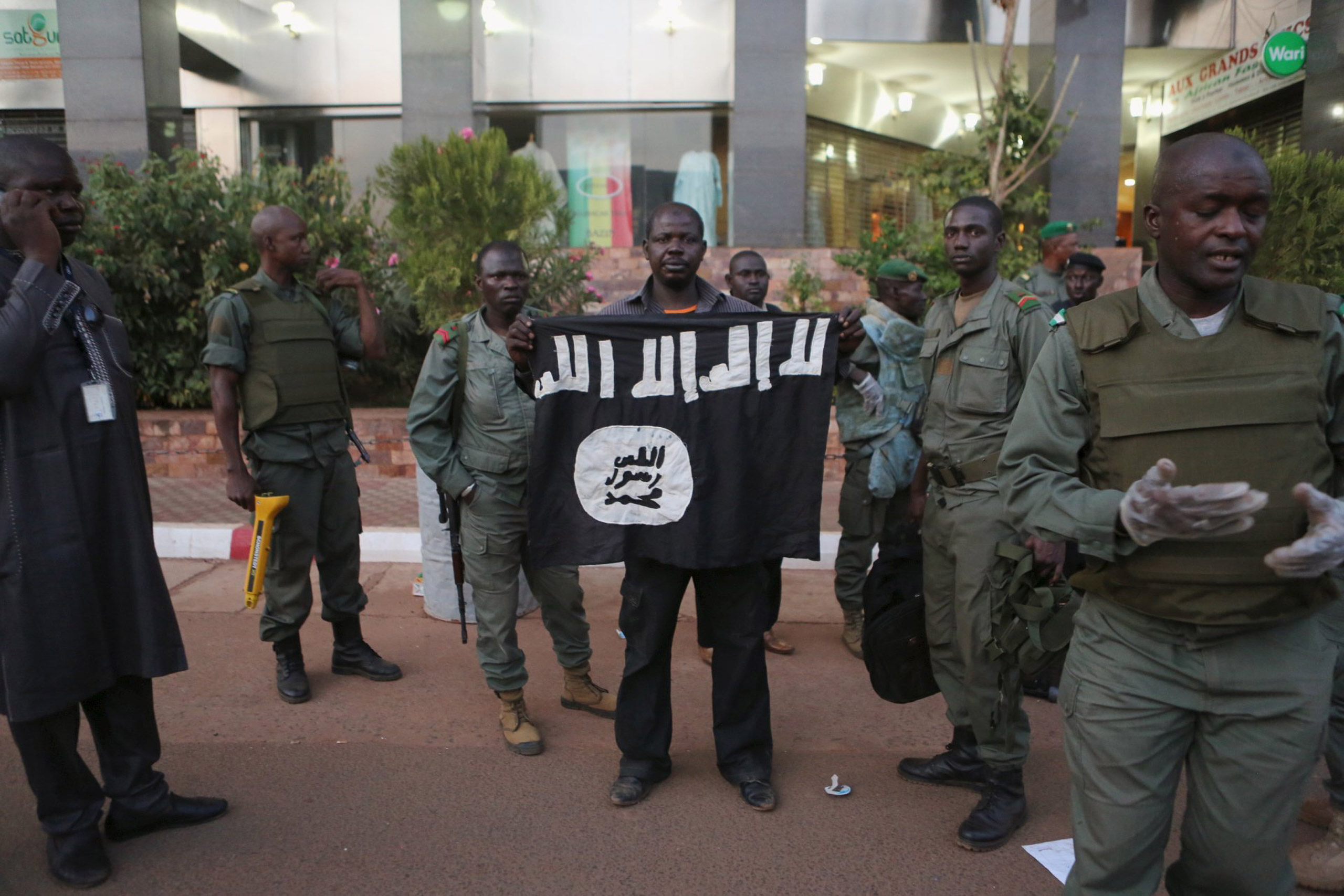Malian security officials show a jihadist flag they said belonged to attackers in front of the Radisson hotel in Bamako, Mali, on Nov. 20, 2015.