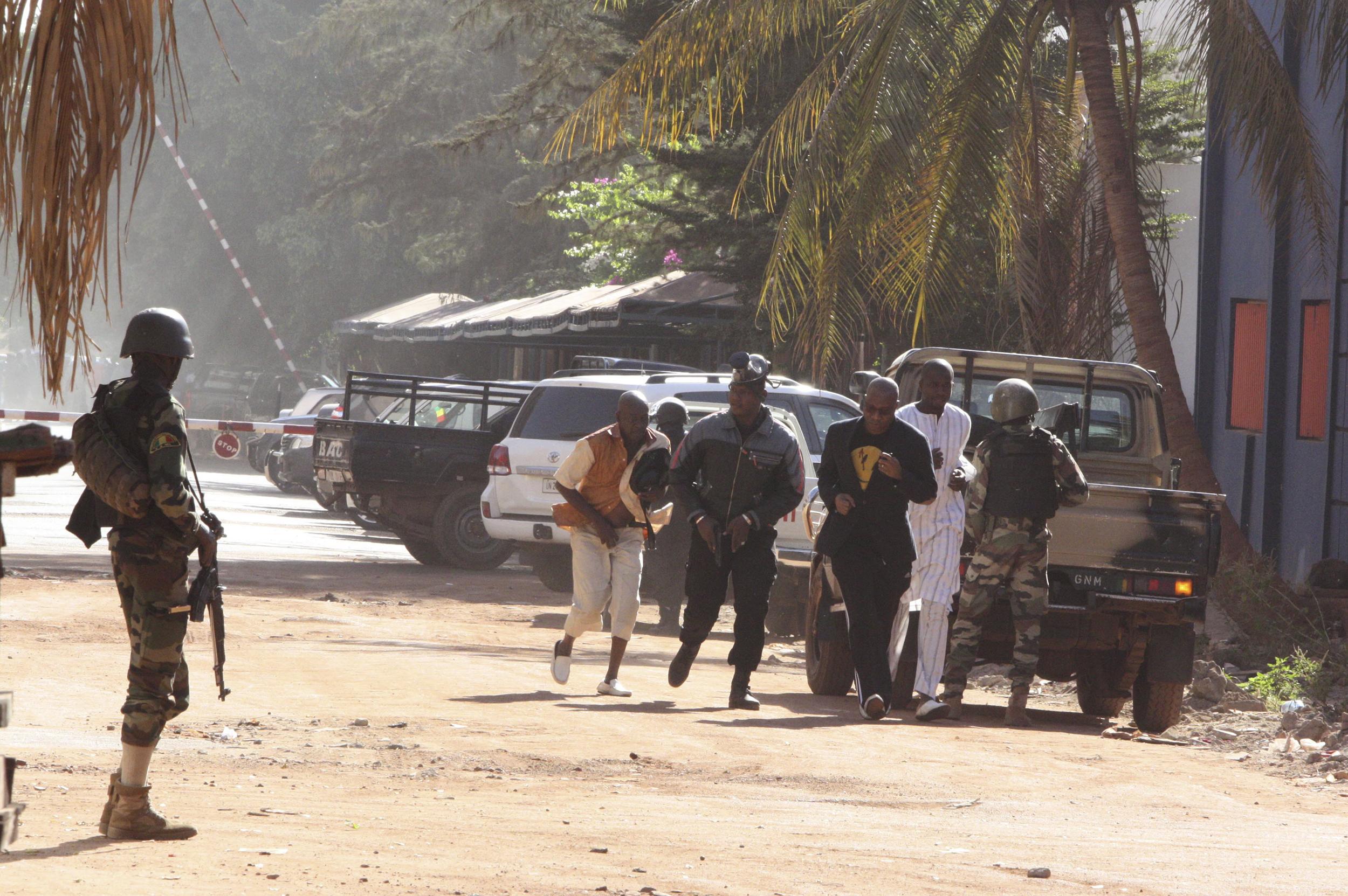 People run to flee from the Radisson Blu Hotel in Bamako, Mali on Nov. 20, 2015.