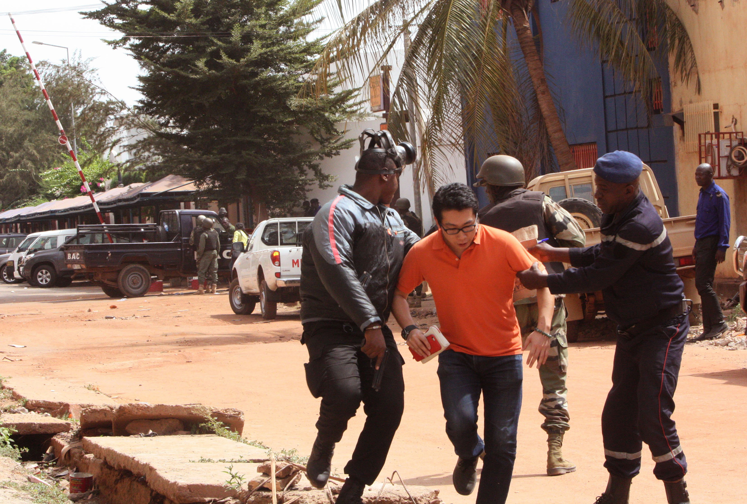 Mali trooper assist a hostage to leave the scene, from the Radisson Blu hotel to safety after gunmen attacked the hotel in Bamako, Mali on Nov. 20, 2015.