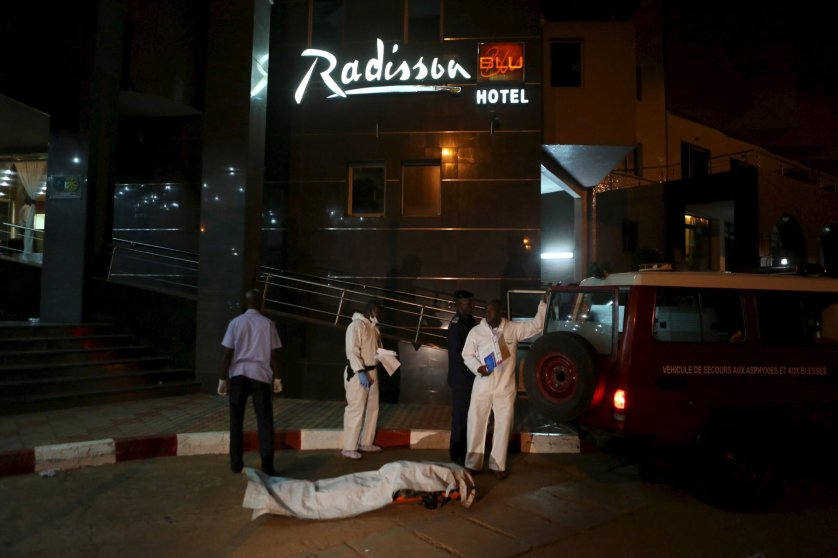 Malian officials prepare to lift a corpse into an emergency vehicle outside the Radisson hotel in Bamako