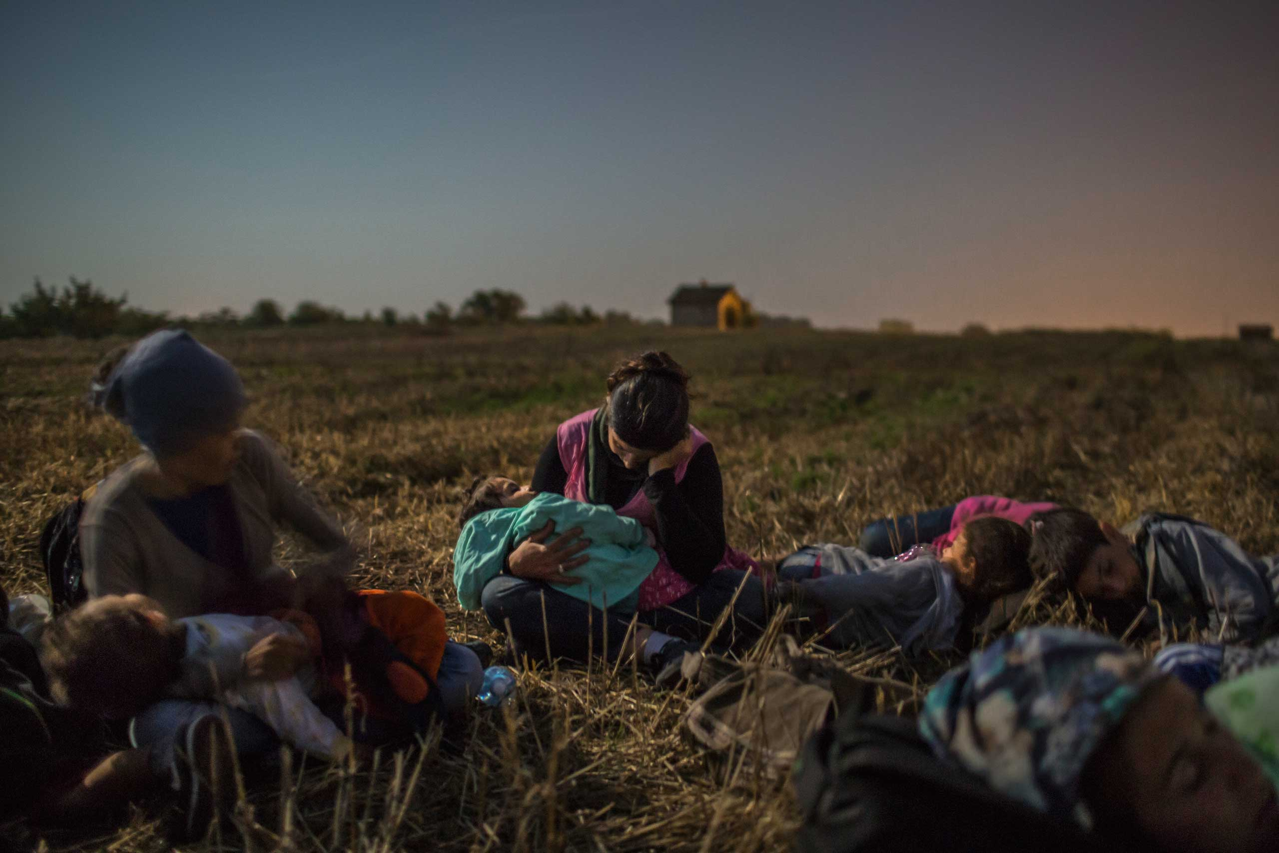 The New York Times: A Family Swept Up in the Migrant TideRojin Shikho, center, wife of Farid Majid, sleeps with her daughter, Widad, among other relatives in a wheat field as they wait to cross barbed wire from Horgos, Serbia, into Hungary, Aug. 31, 2015.