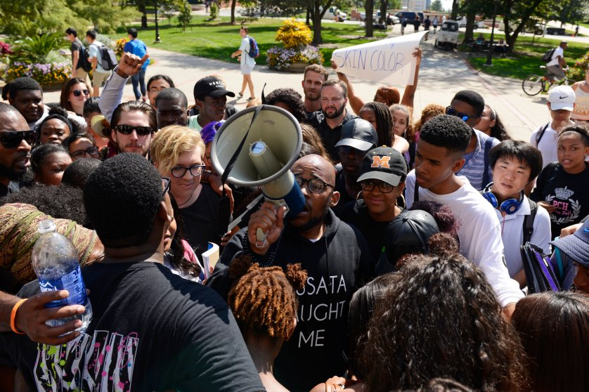 Students gather around graduate student Jonathan Butler for a group hug after marching into Jesse Hall on the University of Missouri campus in Columbia, Mo. on Sept. 24, 2015.