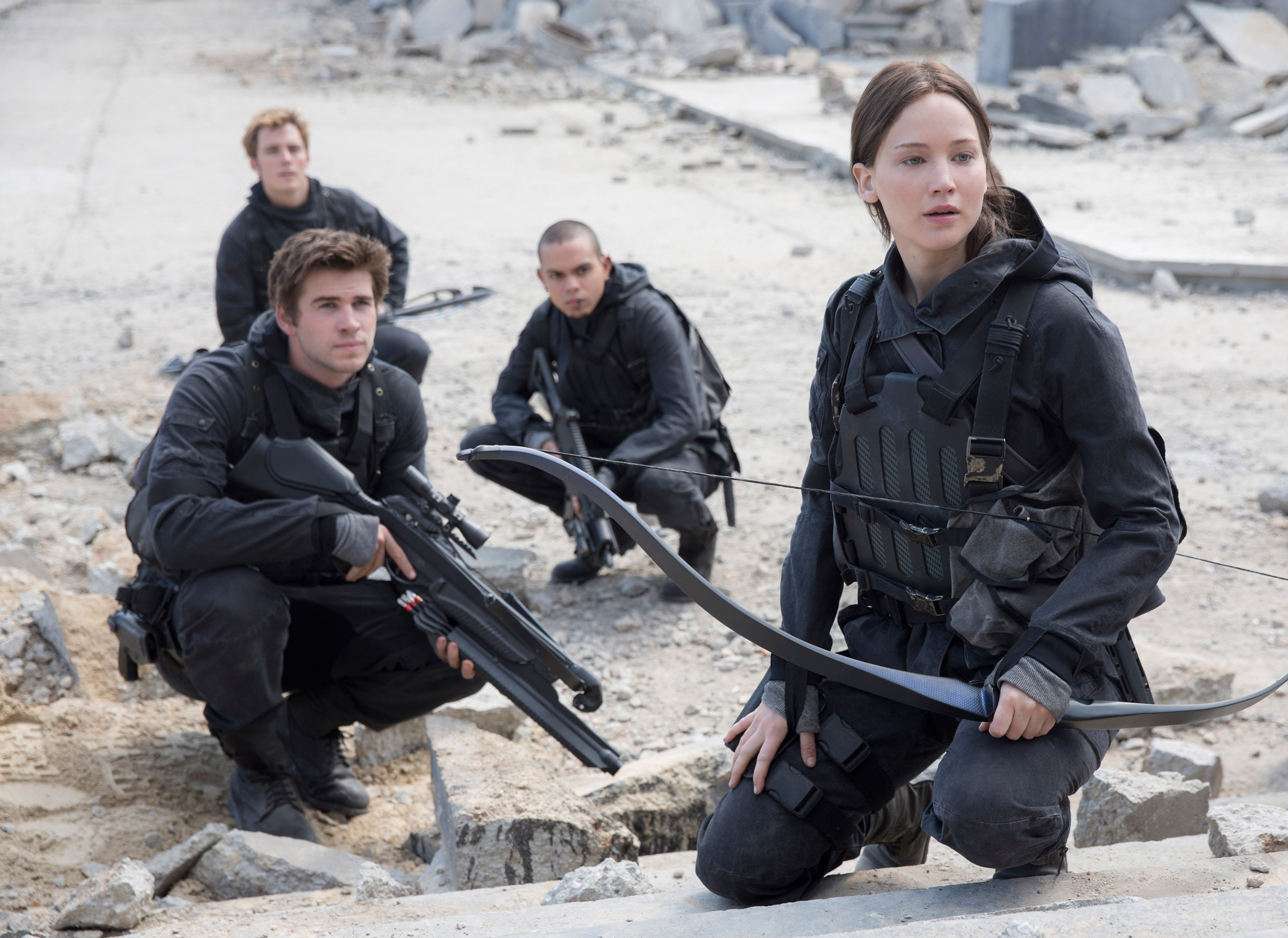 Liam Hemsworth, left, Sam Clafin, back left, Evan Ross, back right, and Jennifer Lawrence, right, in the film,  The Hunger Games: Mockingjay - Part 2.