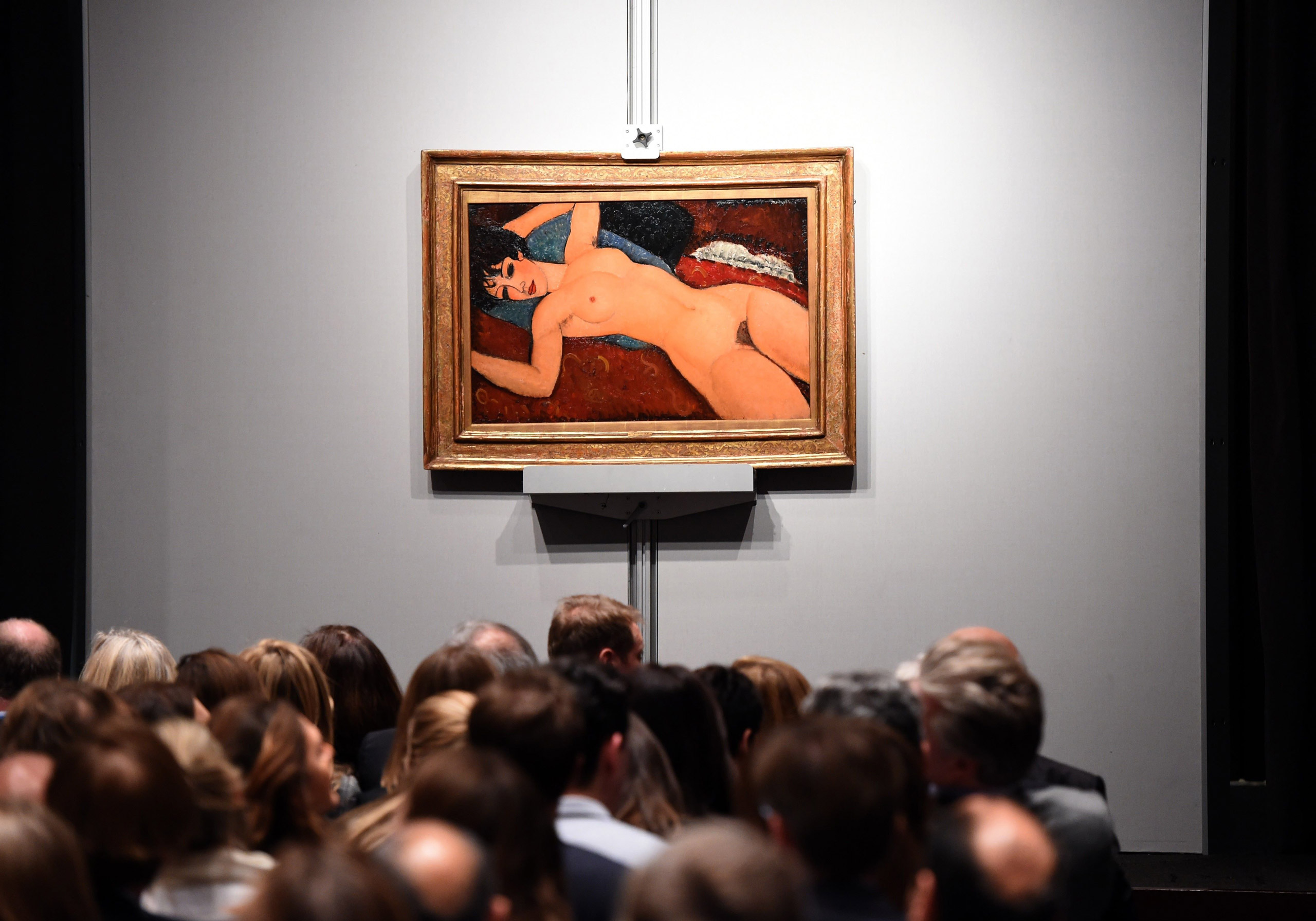 Crowds sit in front of Amedeo Modigliani's  Nu couche  during the  Artist Muse: A Curated Evening Sale  at Christie's in New York on Nov. 9, 2015.