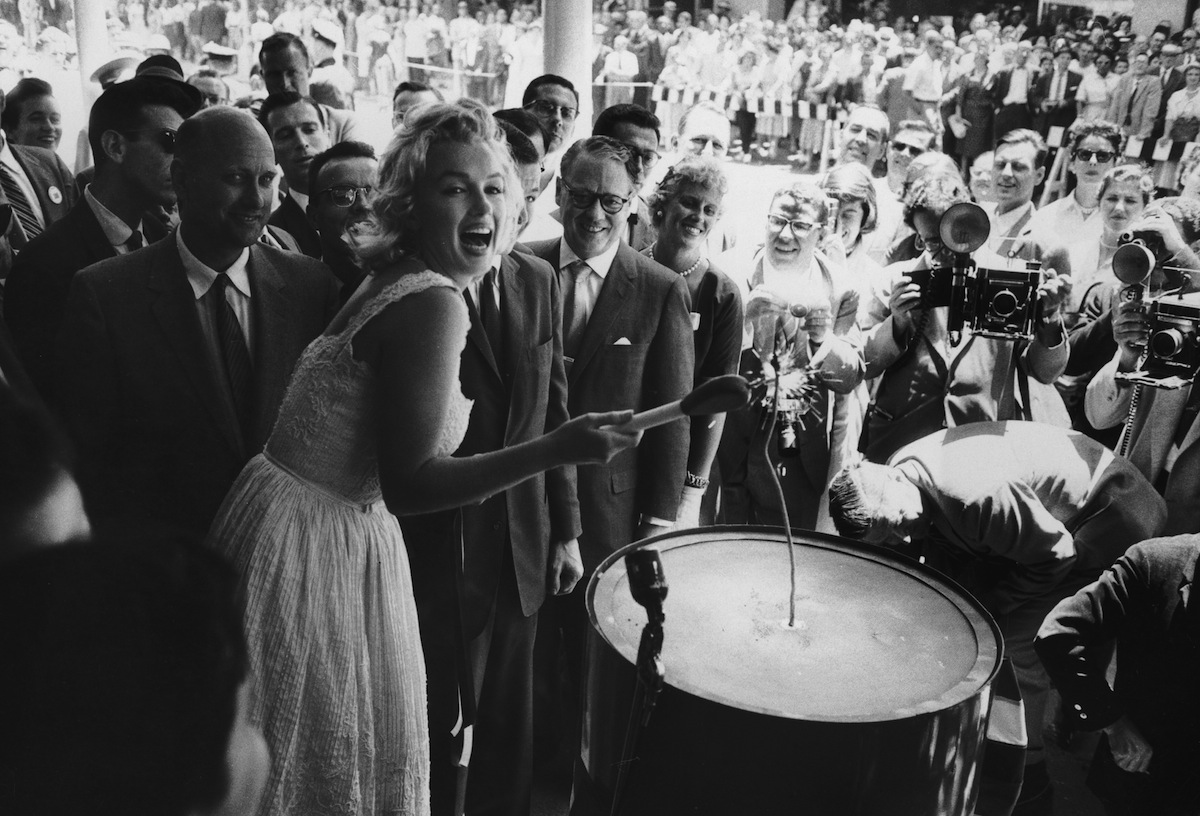 Circa 1960:  American actor Marilyn Monroe (1926 - 1962) uses an outsize match to light a large firecracker during the ribbon cutting ceremony at the Time-Life Building in New York City.