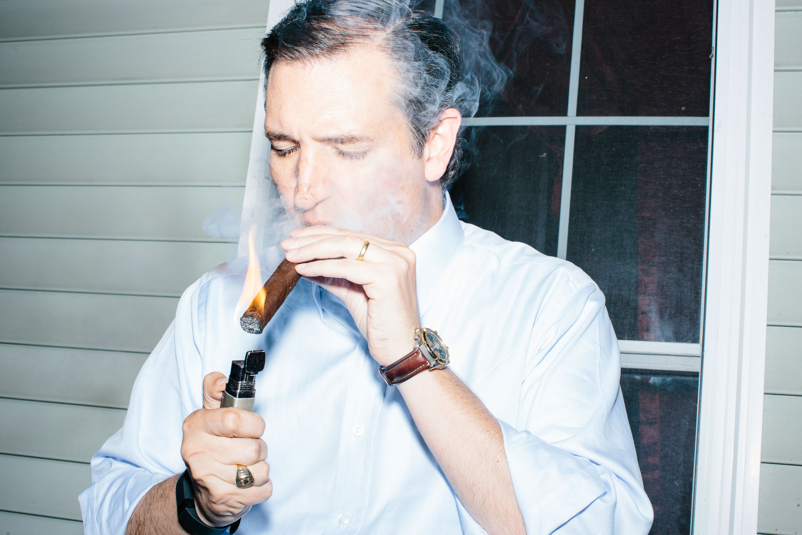 Texas senator and Republican presidential candidate Ted Cruz smokes a cigar after speaking at an event called  Smoke a cigar with Ted Cruz  at a house party at the home of Linda and Steven Goddu in Salem, N.H.