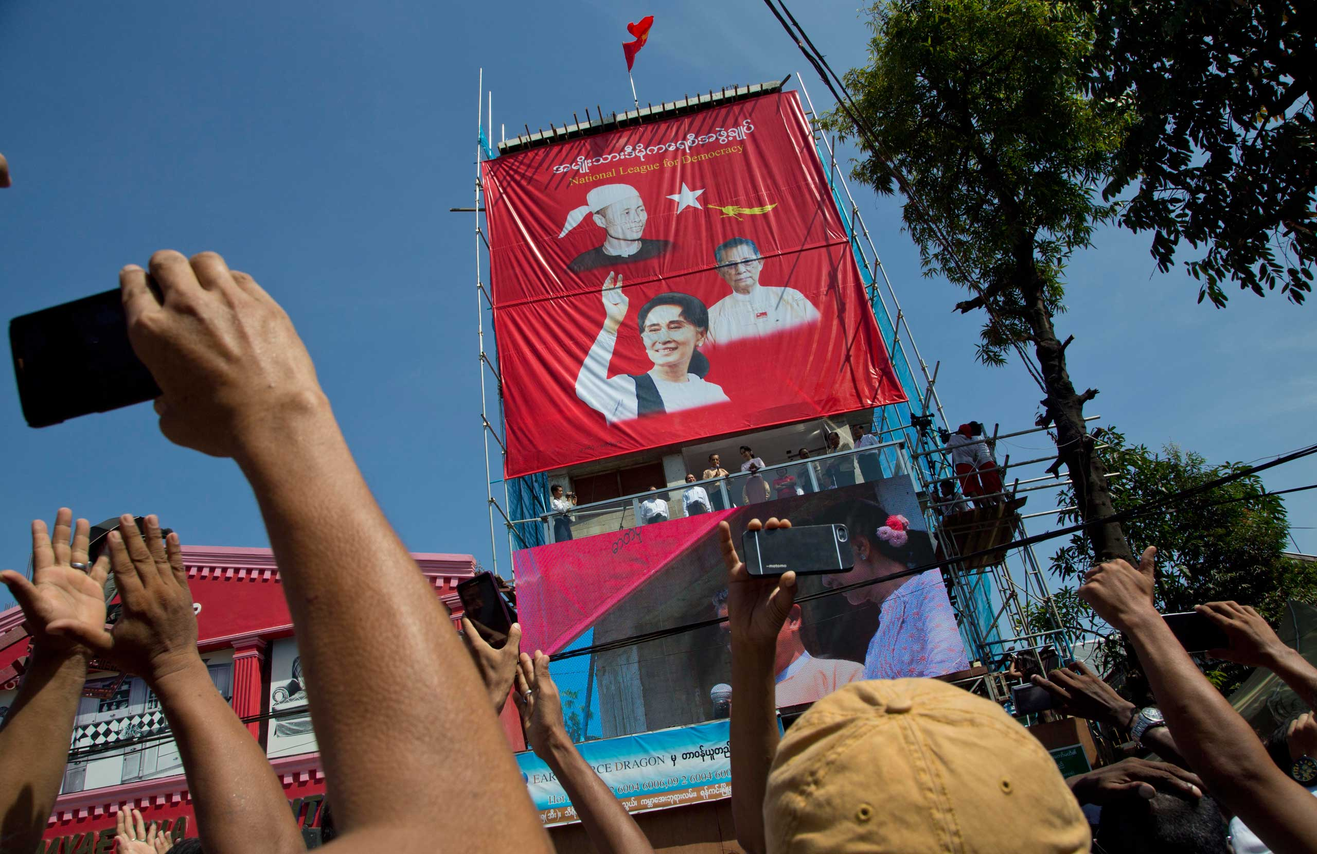 Supporters clap and take pictures from their mobile phone cameras as Burma's opposition leader Aung San Suu Kyi and patron Tin Oo deliver address the supporters in Rangoon, Burma, on Nov. 9, 2015.
