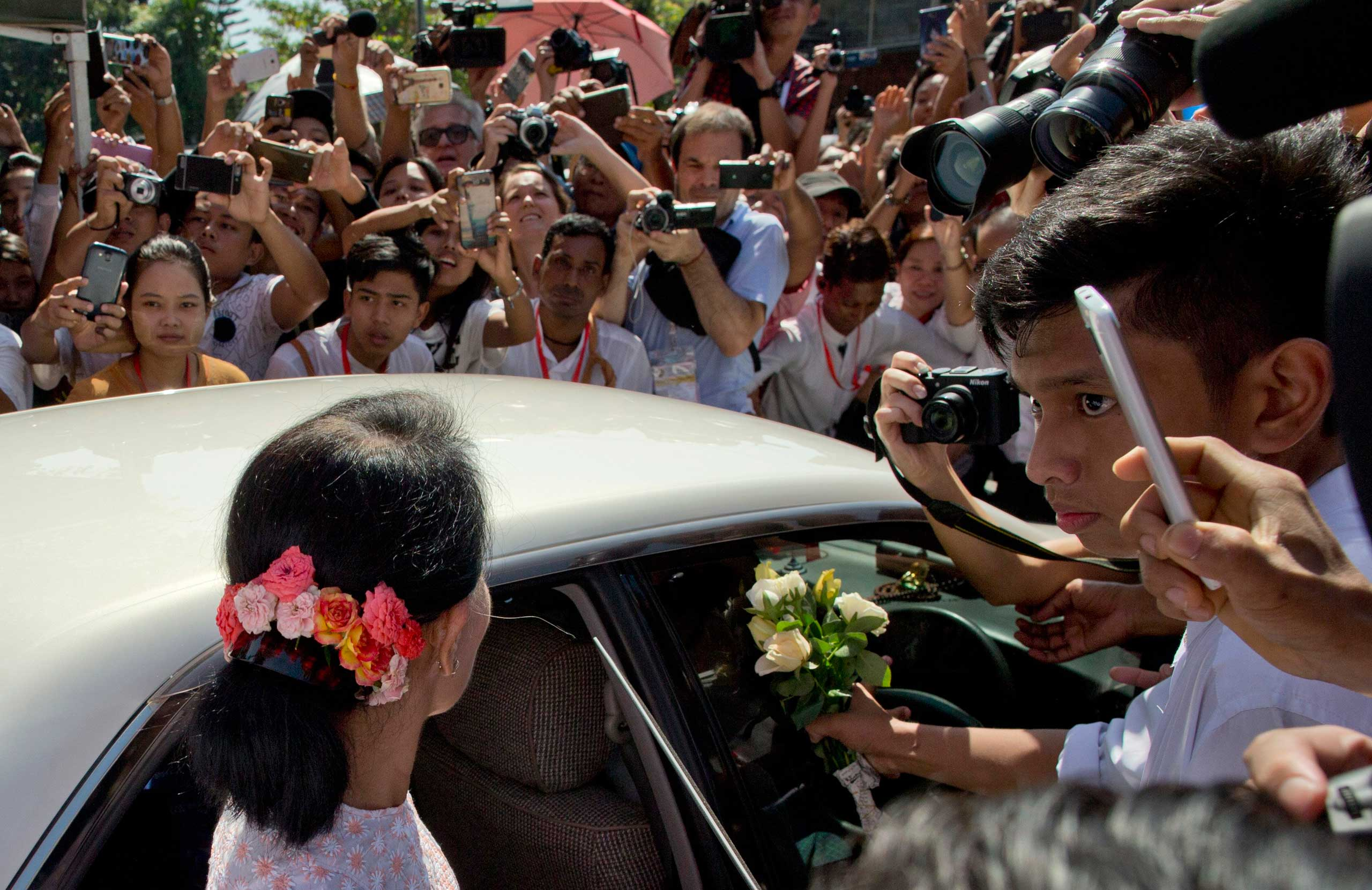 Aung San Suu Kyi with flowers in her hair, leaves after delivering a speech in Rangoon, Burma, on Nov. 9, 2015.